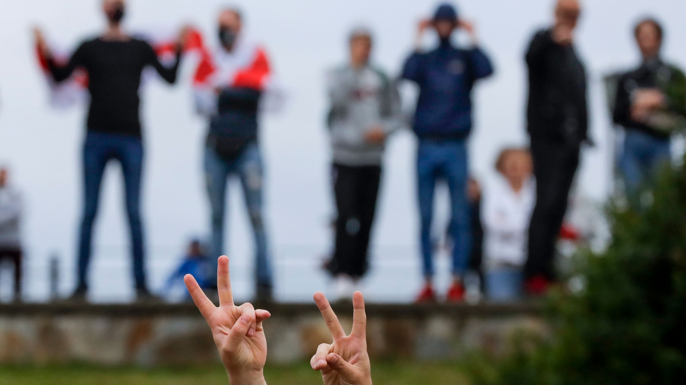 A pair of hands are shown in the nearground flashing peace signs with several people standing in a row in the background.