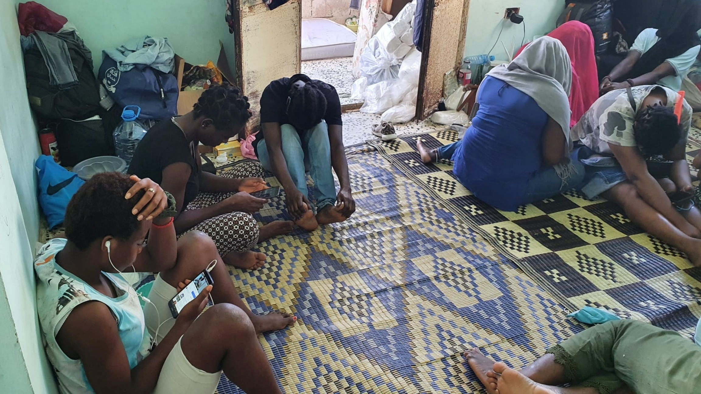 Several African women sit in a room with light blue walls, next to luggage and personal belongings.