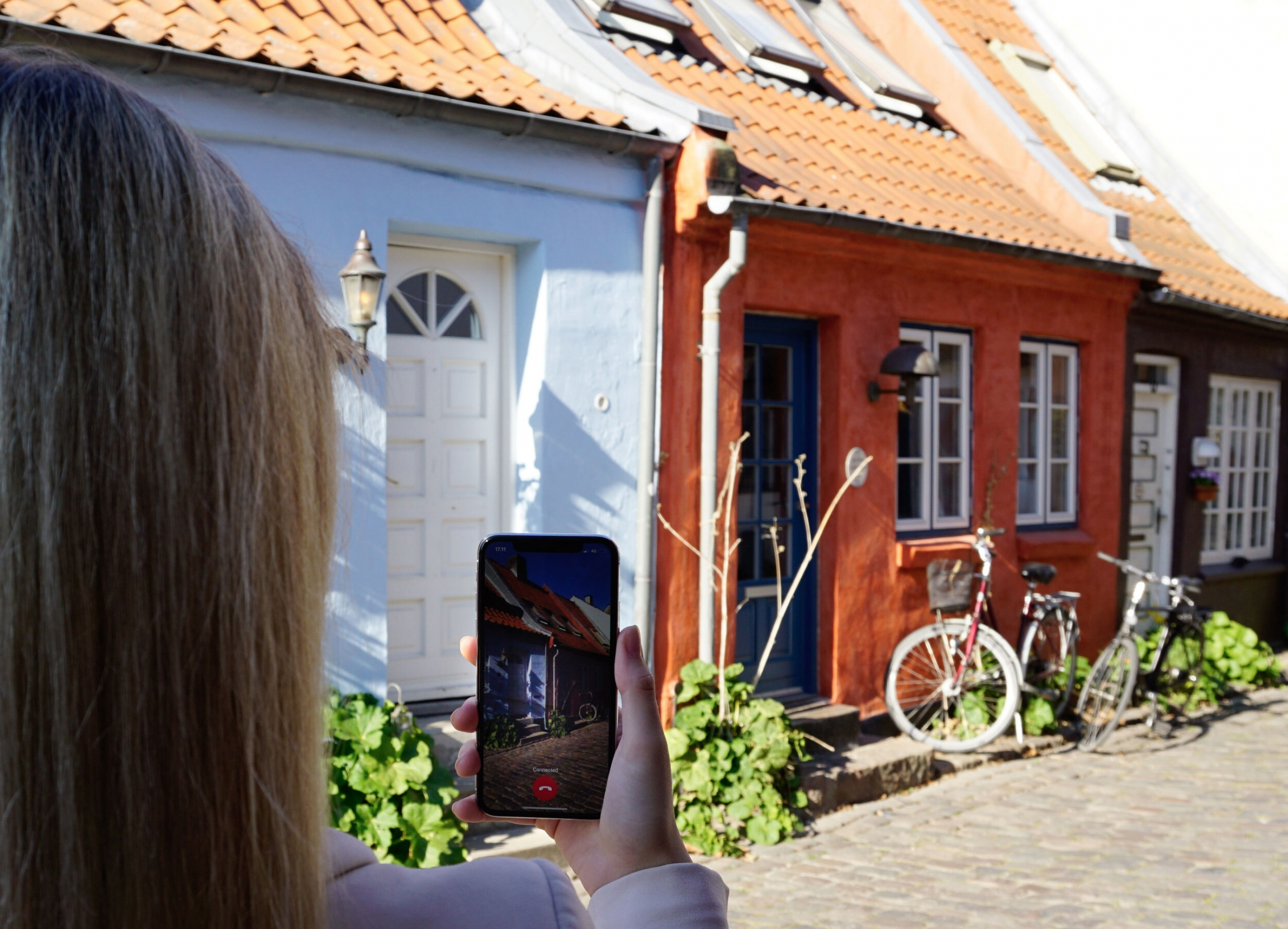A woman uses Be My Eyes video chat app to connect with a sighted volunteer to show a house on a cobblestone street.