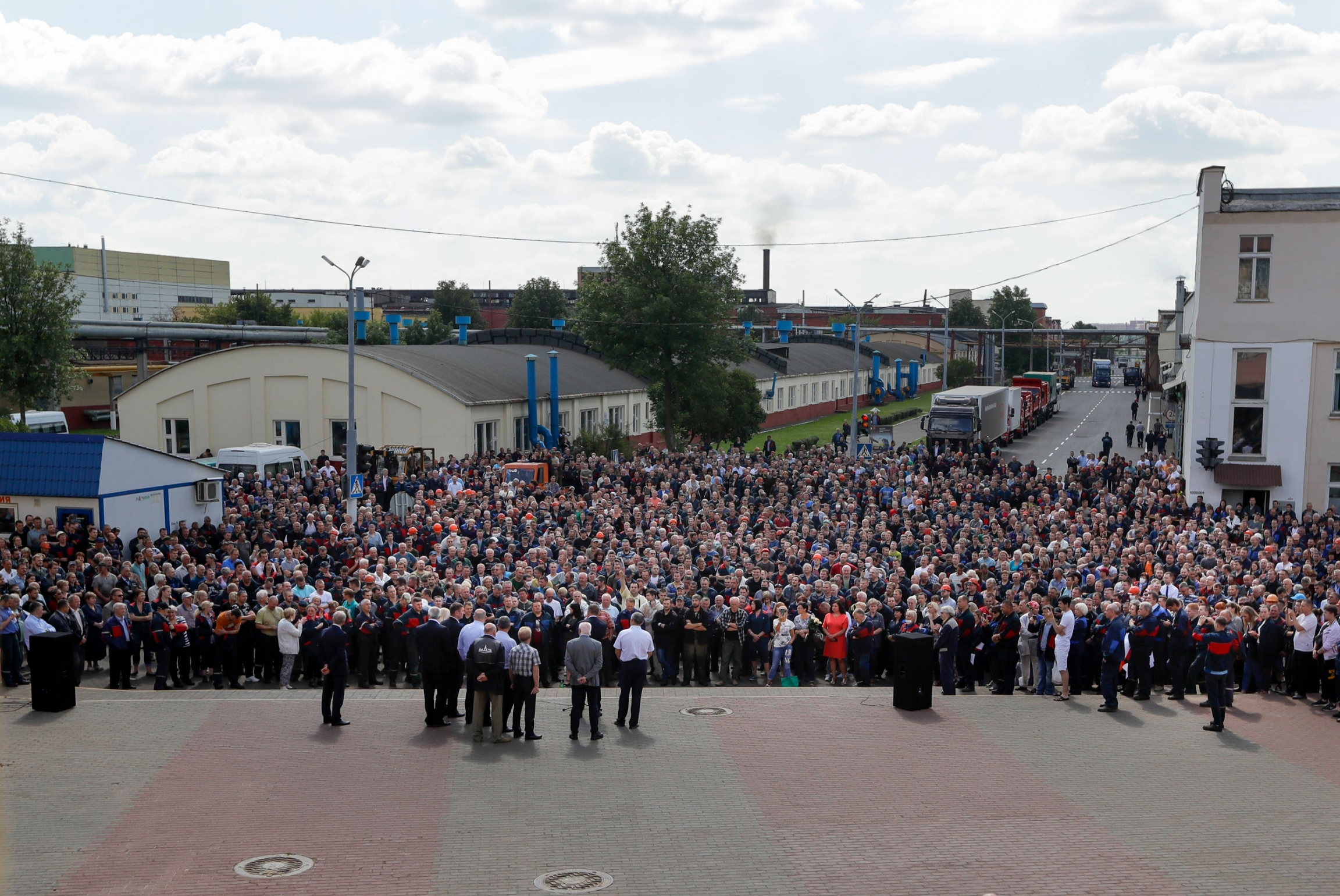 A large crowd of people are shown in the street with a factory in the background.