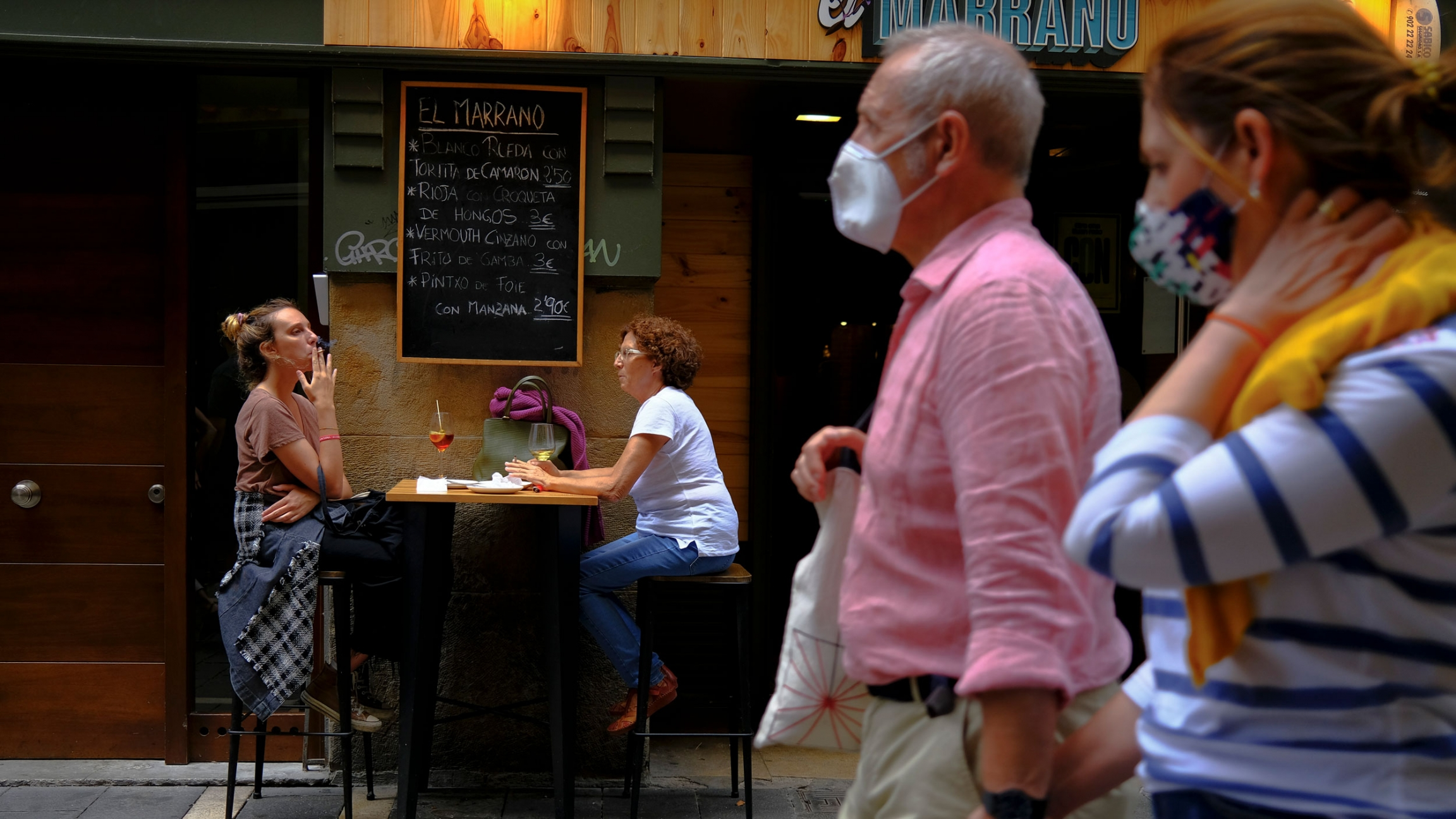 A couple is shown in soft focus walking and wearing face masks with two women shown in the distance sitting at a cafe table and one woman is smoking a cigarette.