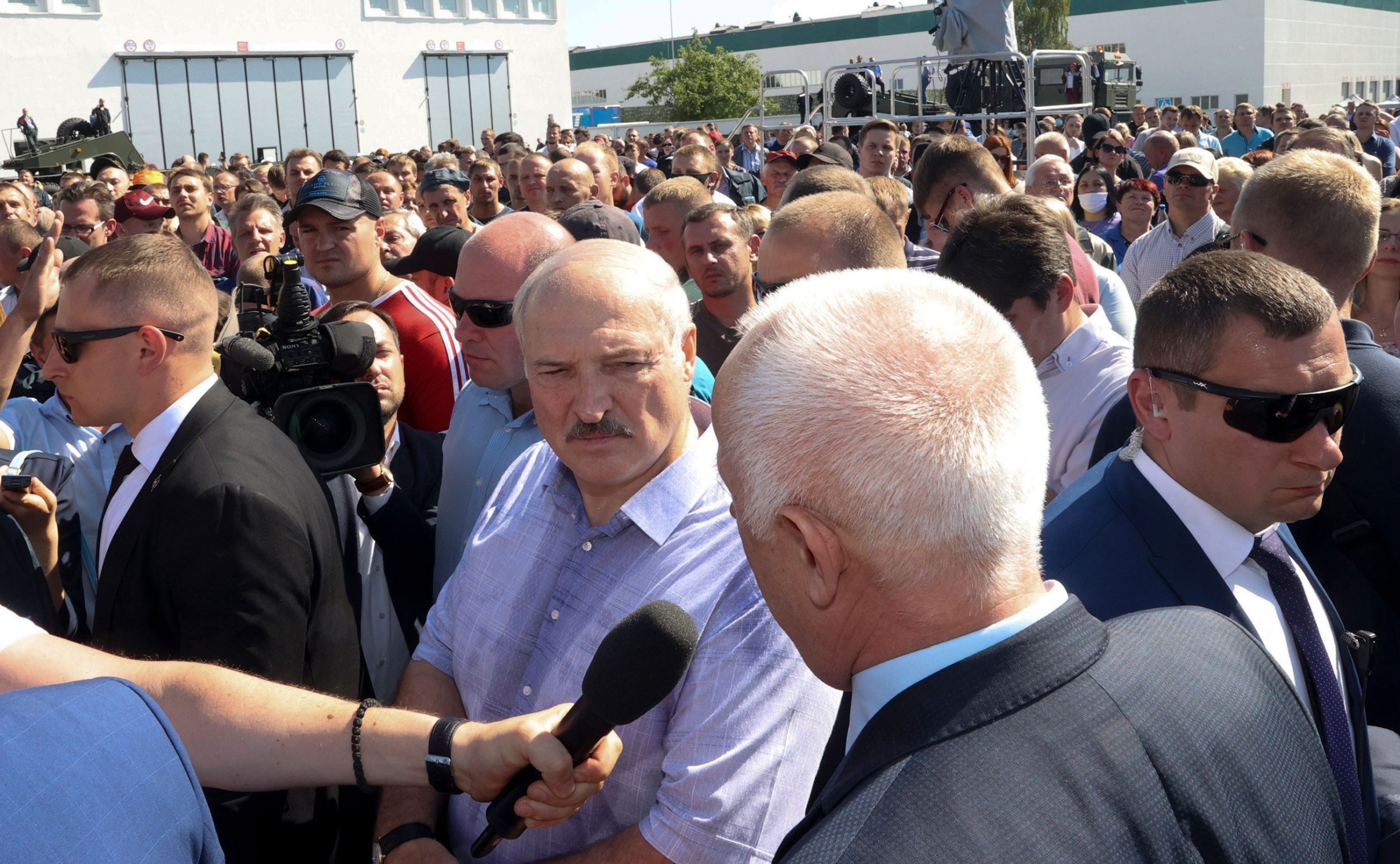 Belarusian President Alexander Lukashenko is shown wearing a blue button down shirt and standing in a large crowd with bodyguards surrounding him.