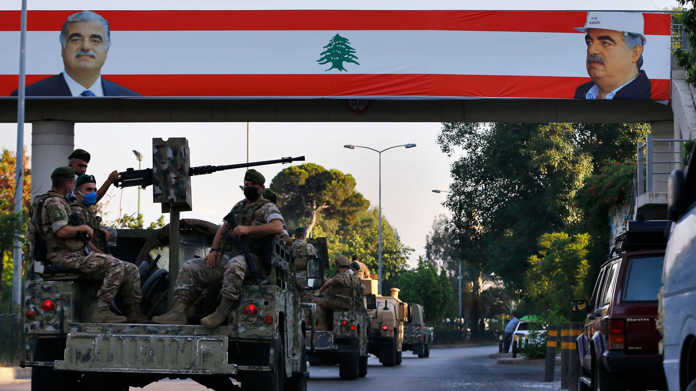 A convoy of military vehicles, some equipped with weapons, pass under a large Lebanese flag with pictures of slain Lebanese Prime Minister Rafik Hariri.