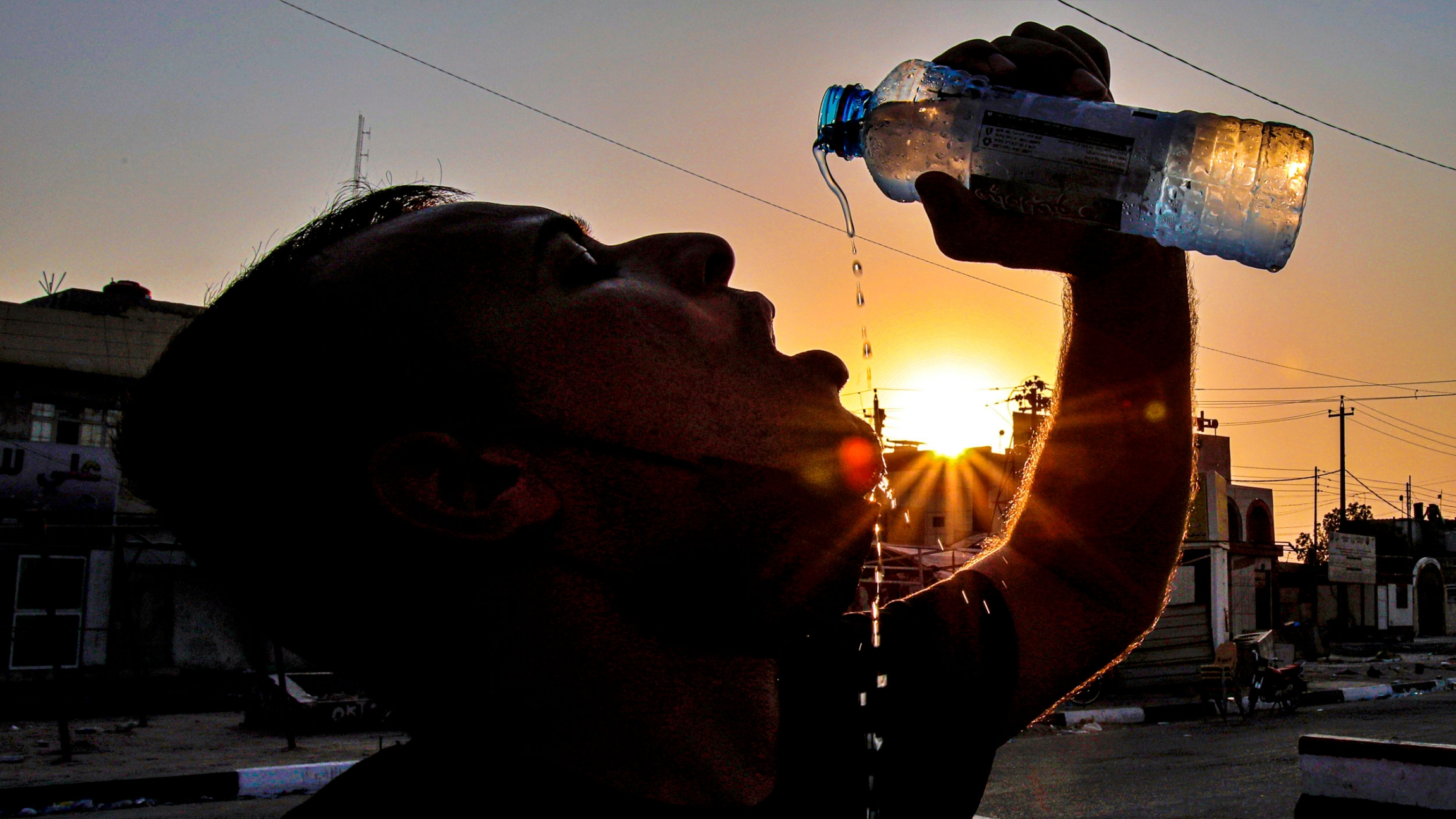 A man is shown in shadow drinking from a water bottle with the sun setting behind him.