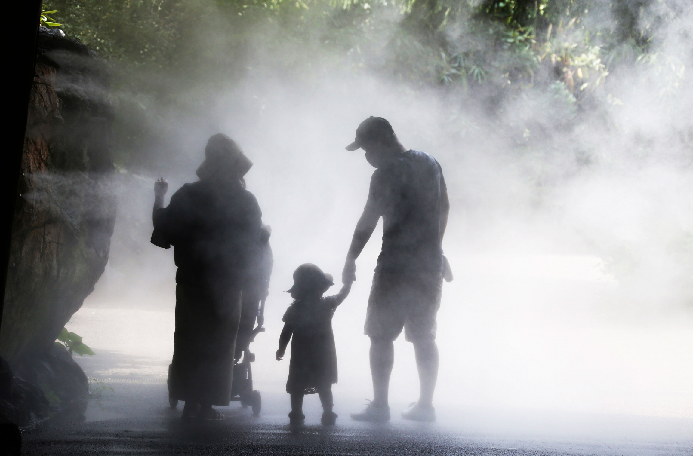 Two people hold the hand of a small child as they are surrounded by mist to cool off.