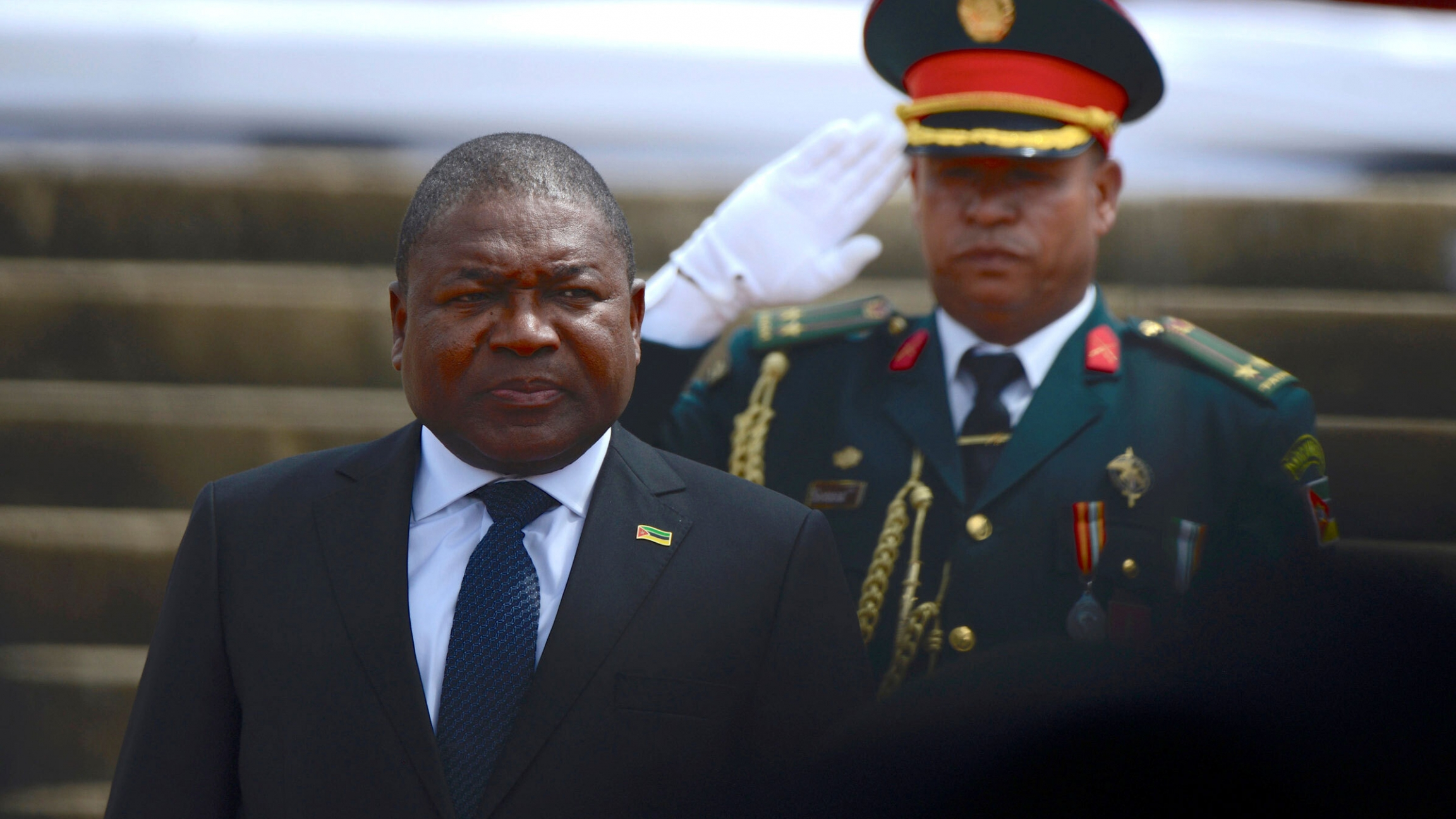 President of Mozambique Filipe Nyusi wears a suit behind a military officer in uniform.