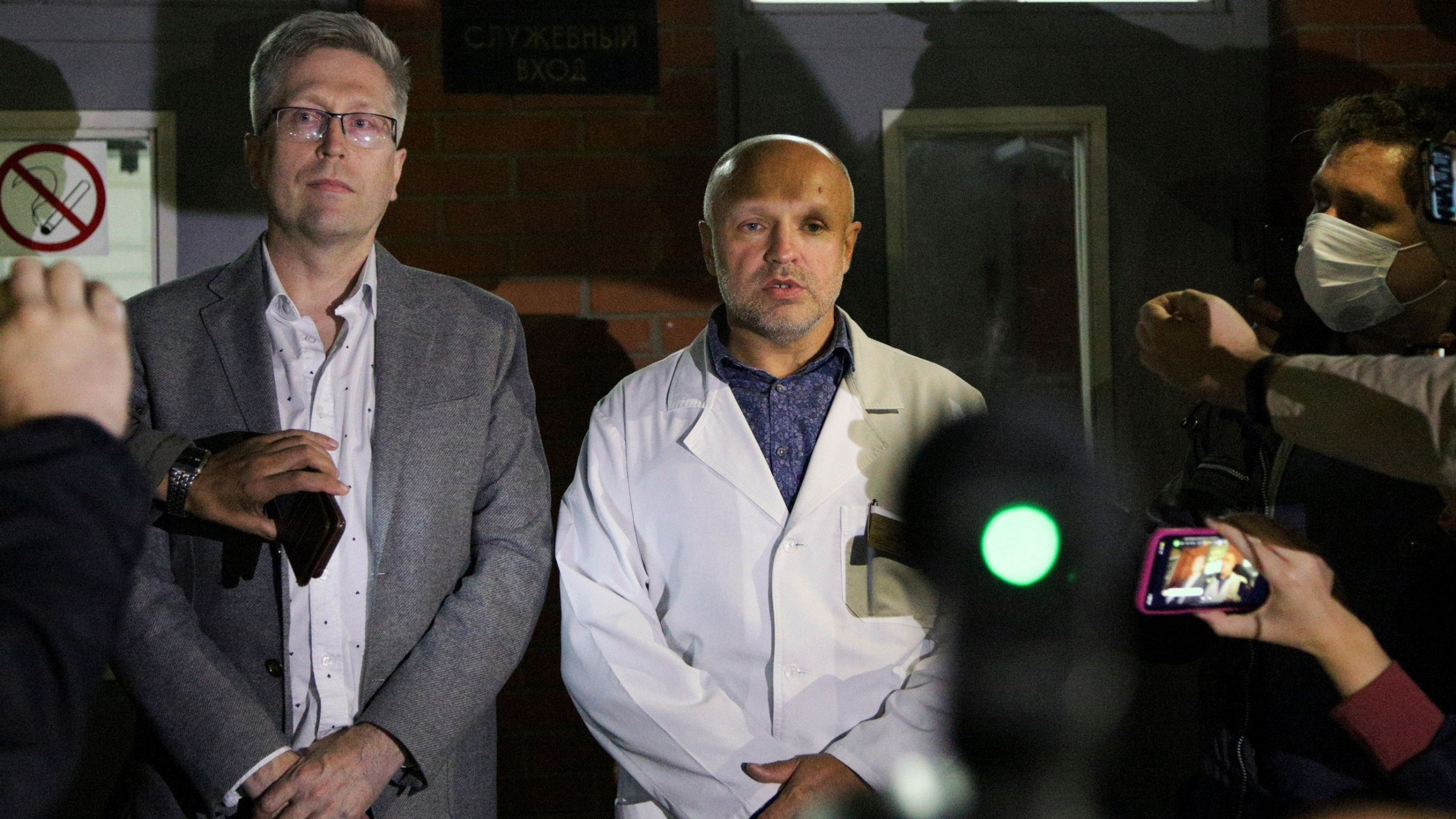 A man is shown standing with his hands folded and wearing a white medical jacket with members of the media nearby.