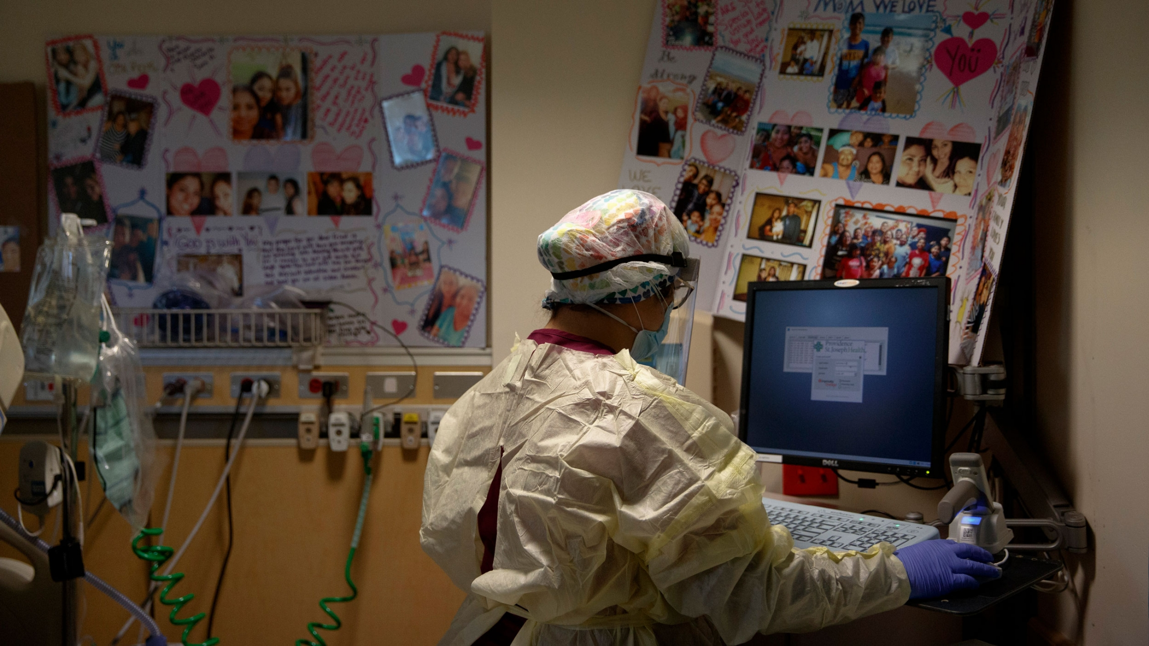 A woman is shown from behind, working on a computer and wearing a nursing cap and gown with get well soon cards on the wall.