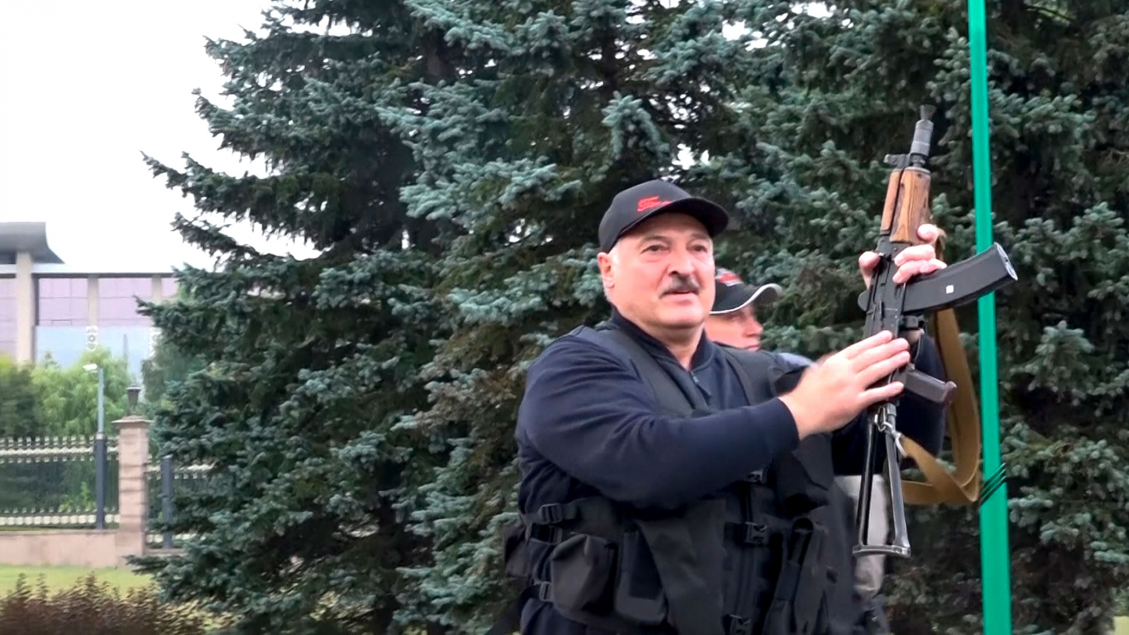 Alexander Lukashenko is shown wearing a hat and black vest while holding an assault rifle in the air.