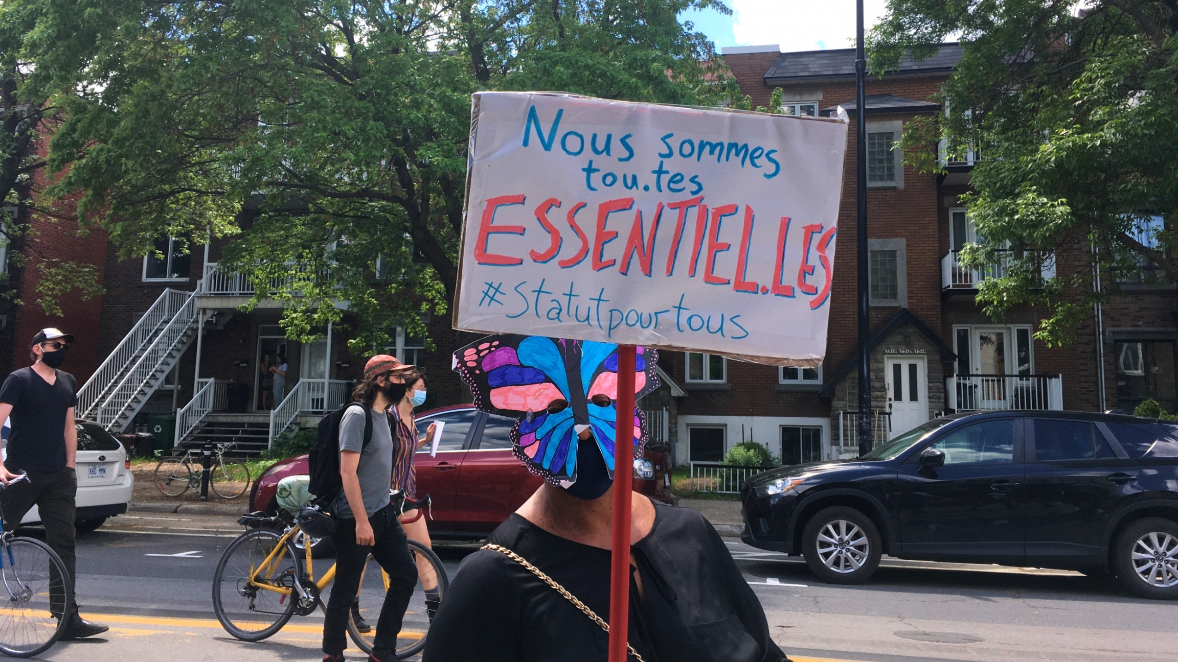 "A demonstrator in Montreal holds up a sign in French saying, ""We are all essential, status for all."""