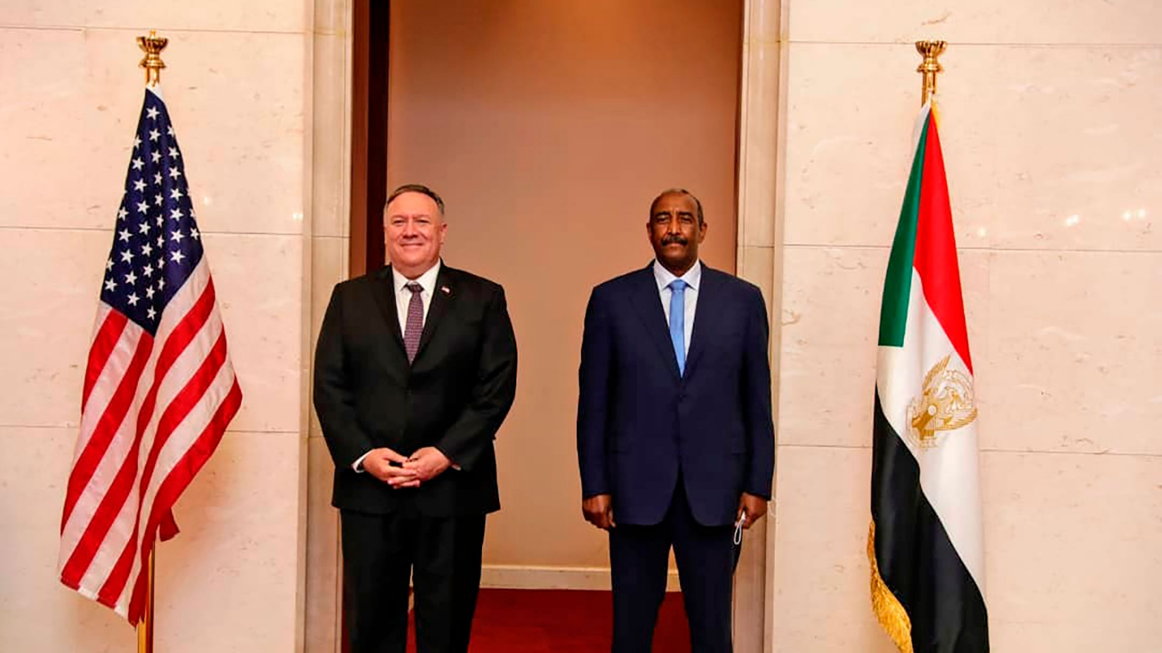 US Secretary of State Mike Pompeo is shown standing with Sudanese Gen. Abdel-Fattah Burhan with the US and Sudanese flags on either side.