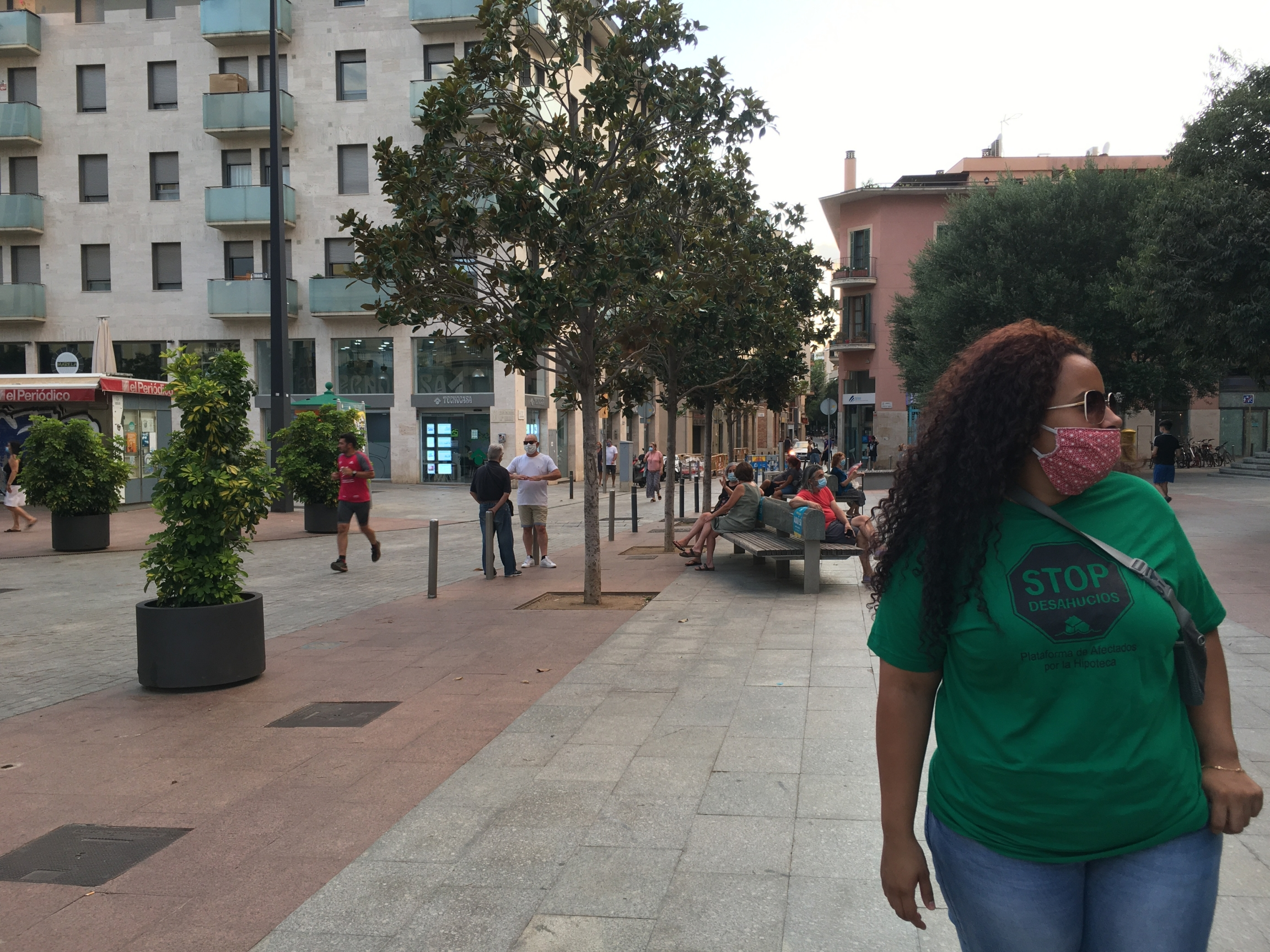 A woman with long brown, curly hair wears a green shirt and jeans as she walks down an urban street.