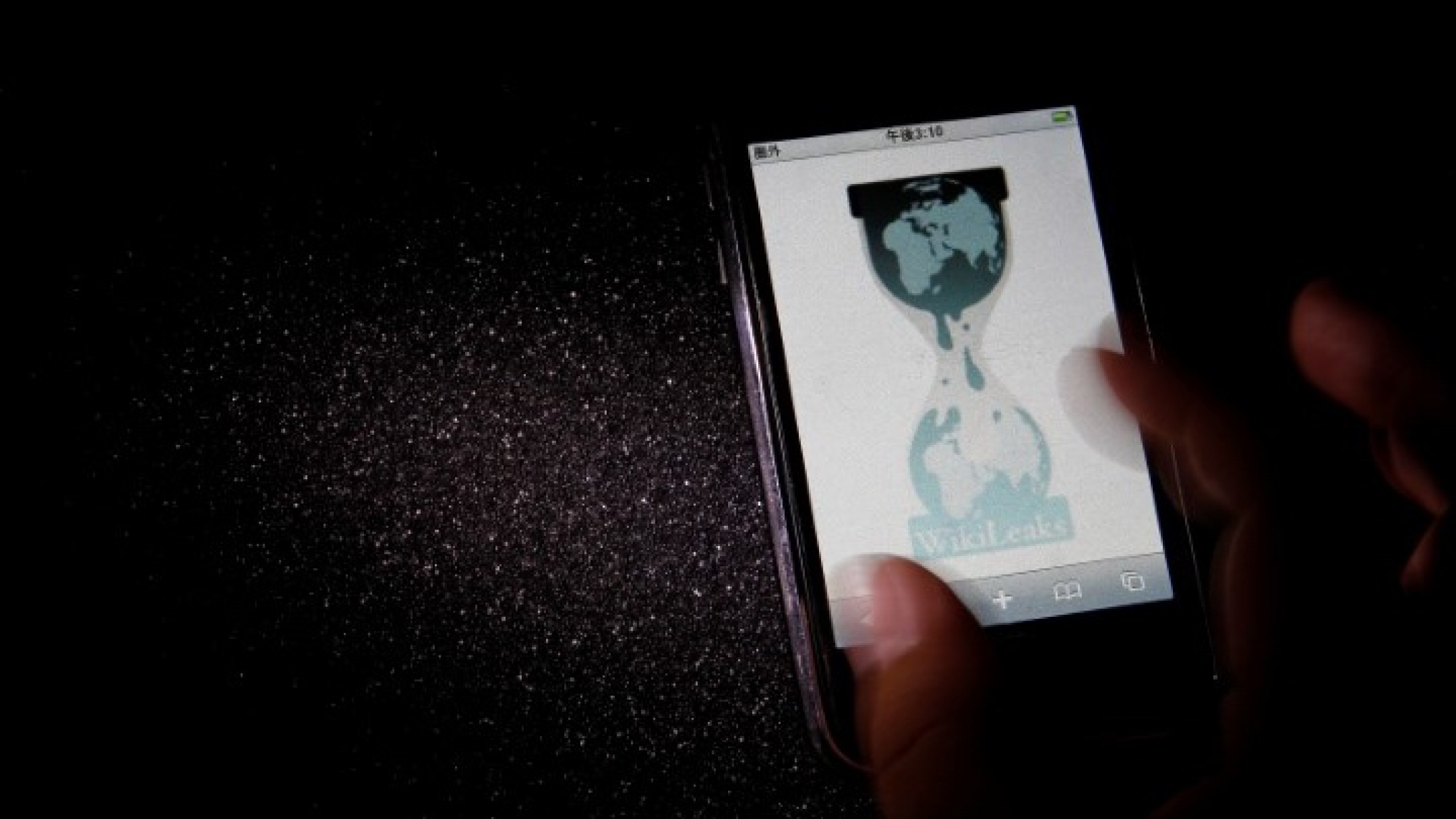 A hand holds a smartphone with Wikileaks webpage logo