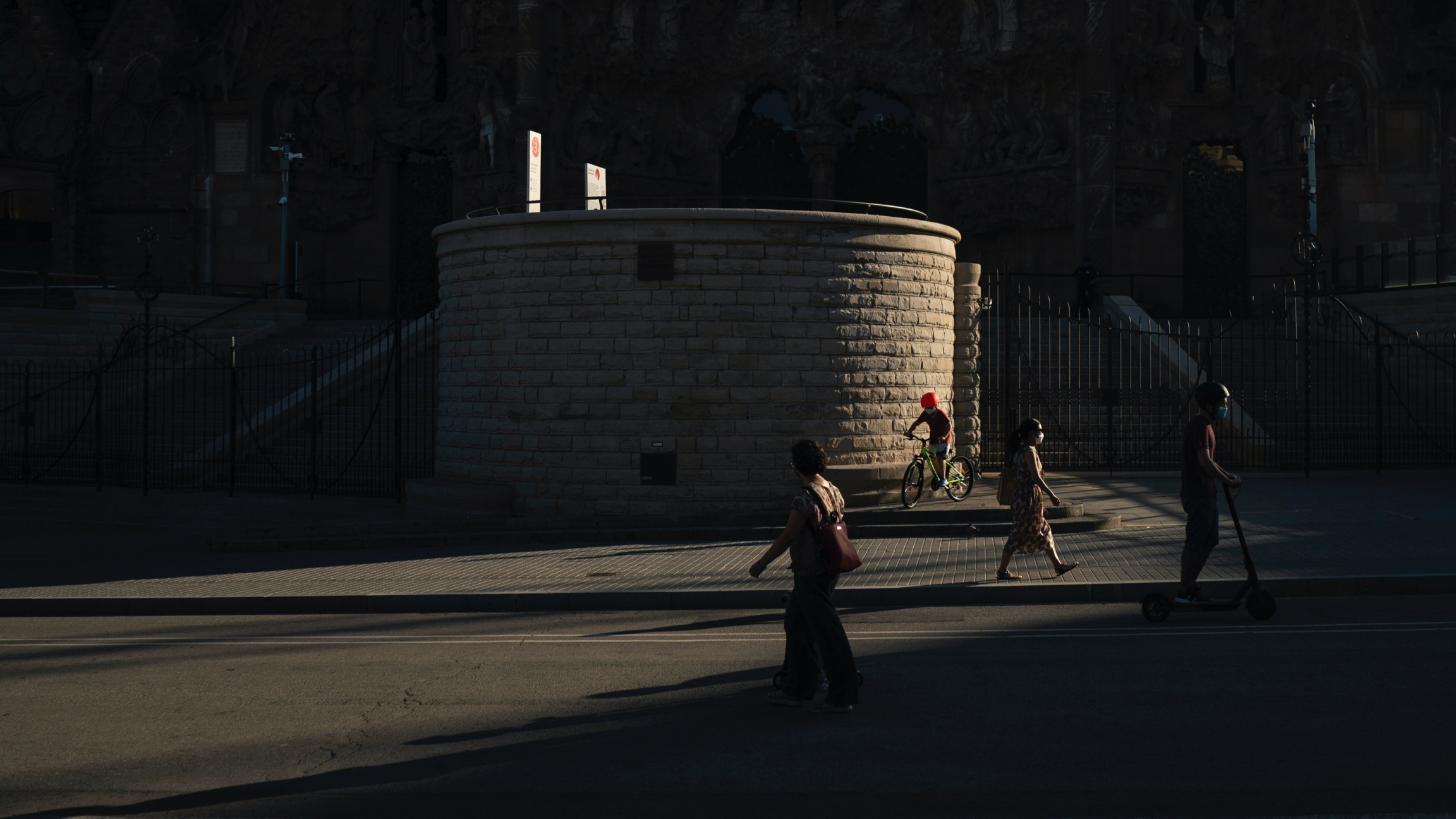 A few people walk or bike in shadows near a large building.