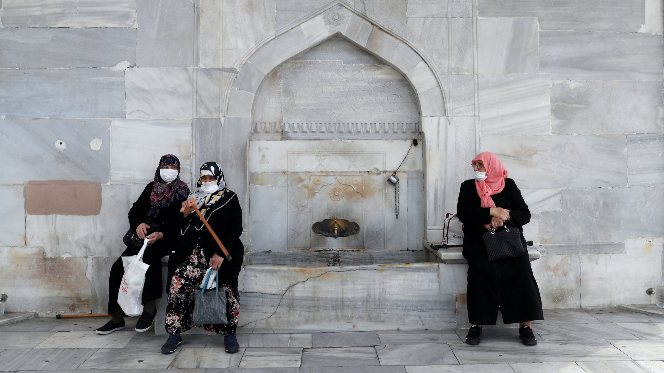 Three women wearing head scarves, long jackets and masks by a gray fountain