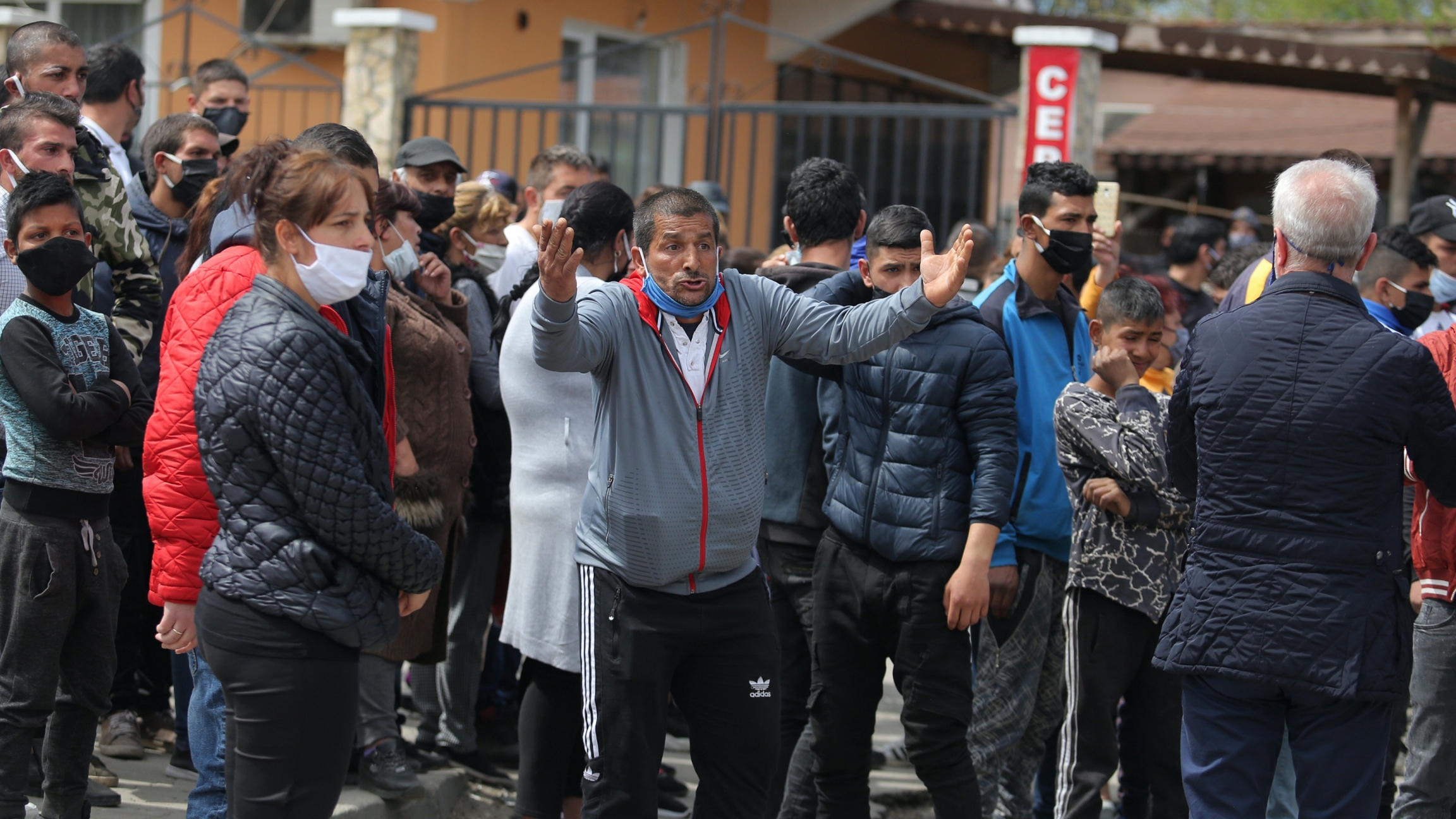 A man reacts with his hand raised amid a large crowd protesting restrictions due to COVID-19.