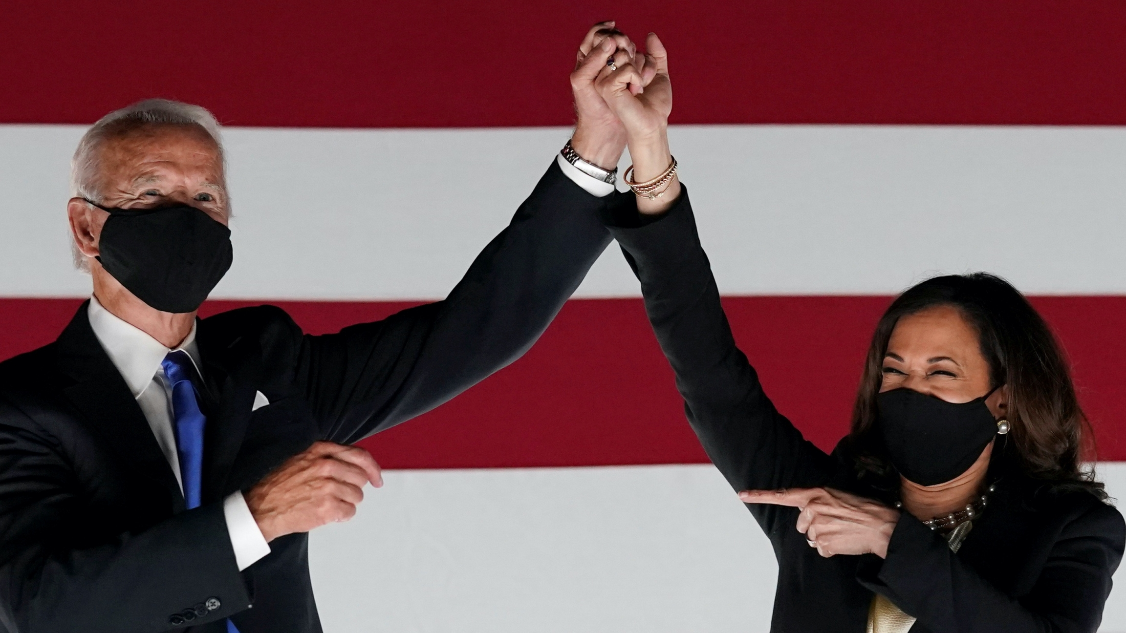 Biden and Harris wear masks, clasp hands, and Harris points at Biden, smiling with her eyes.