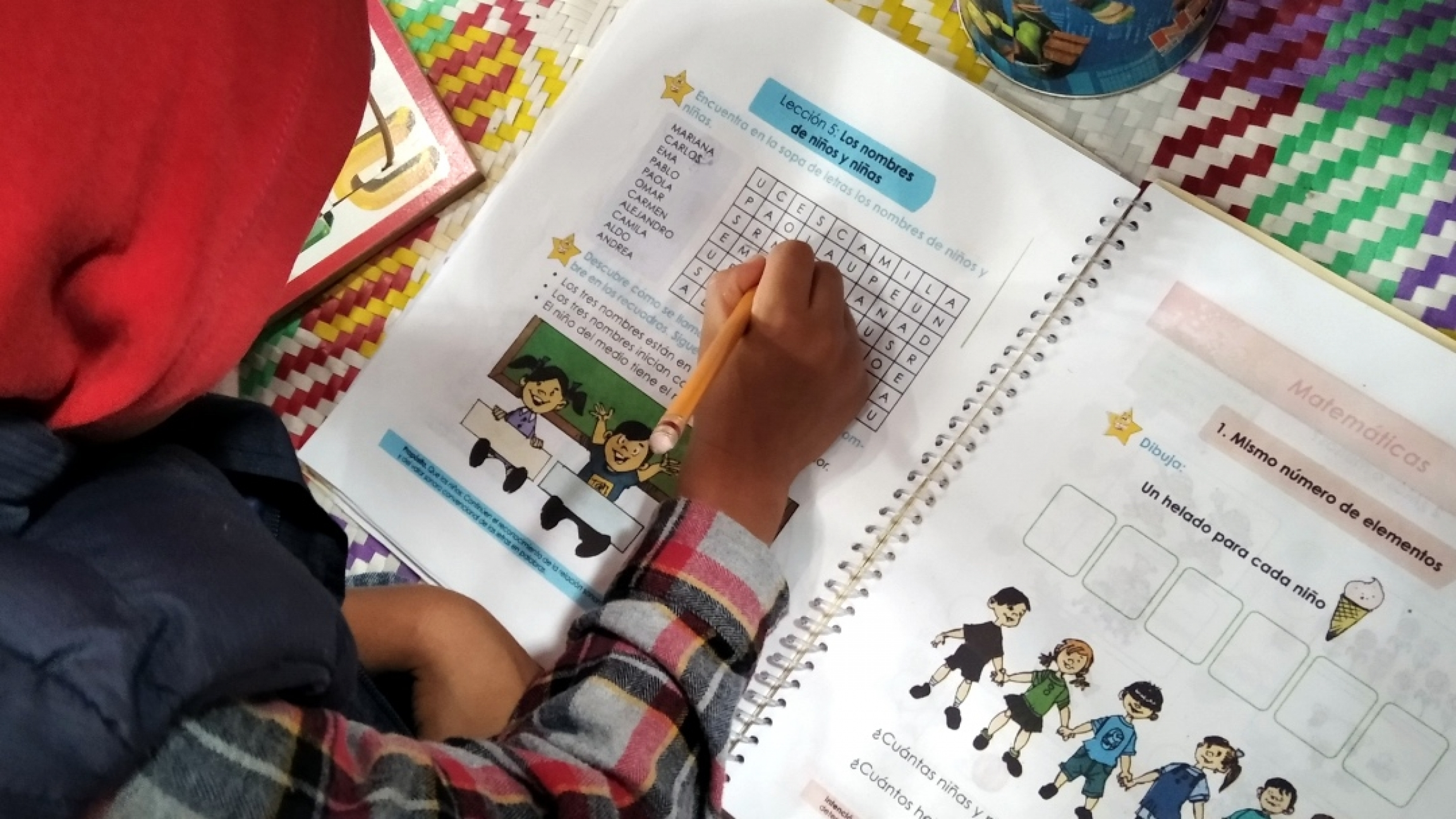 A student hovers over a notebook and fills in a lesson.