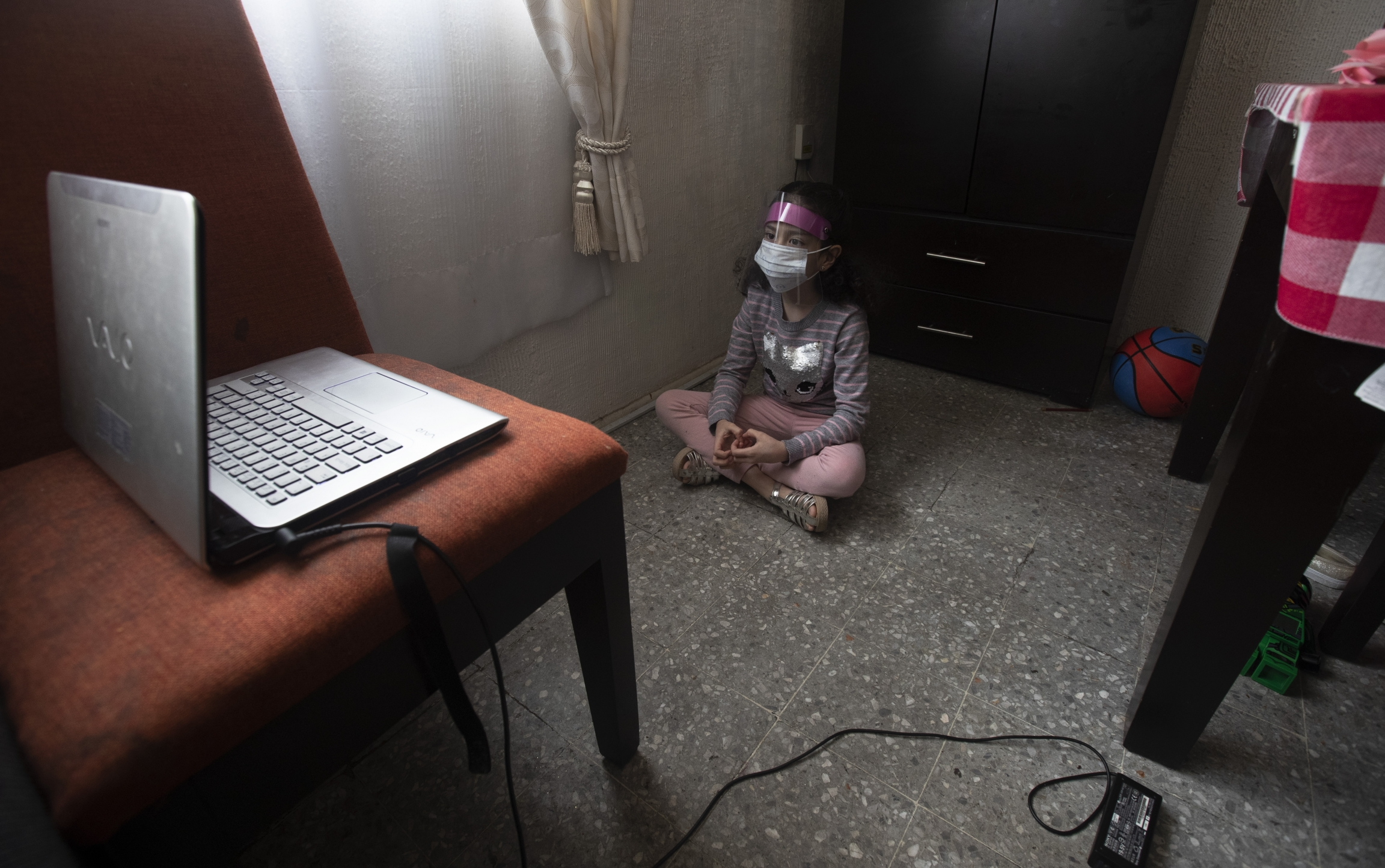 A girl wears a plastic guard indoors as she watches a laptop screen.