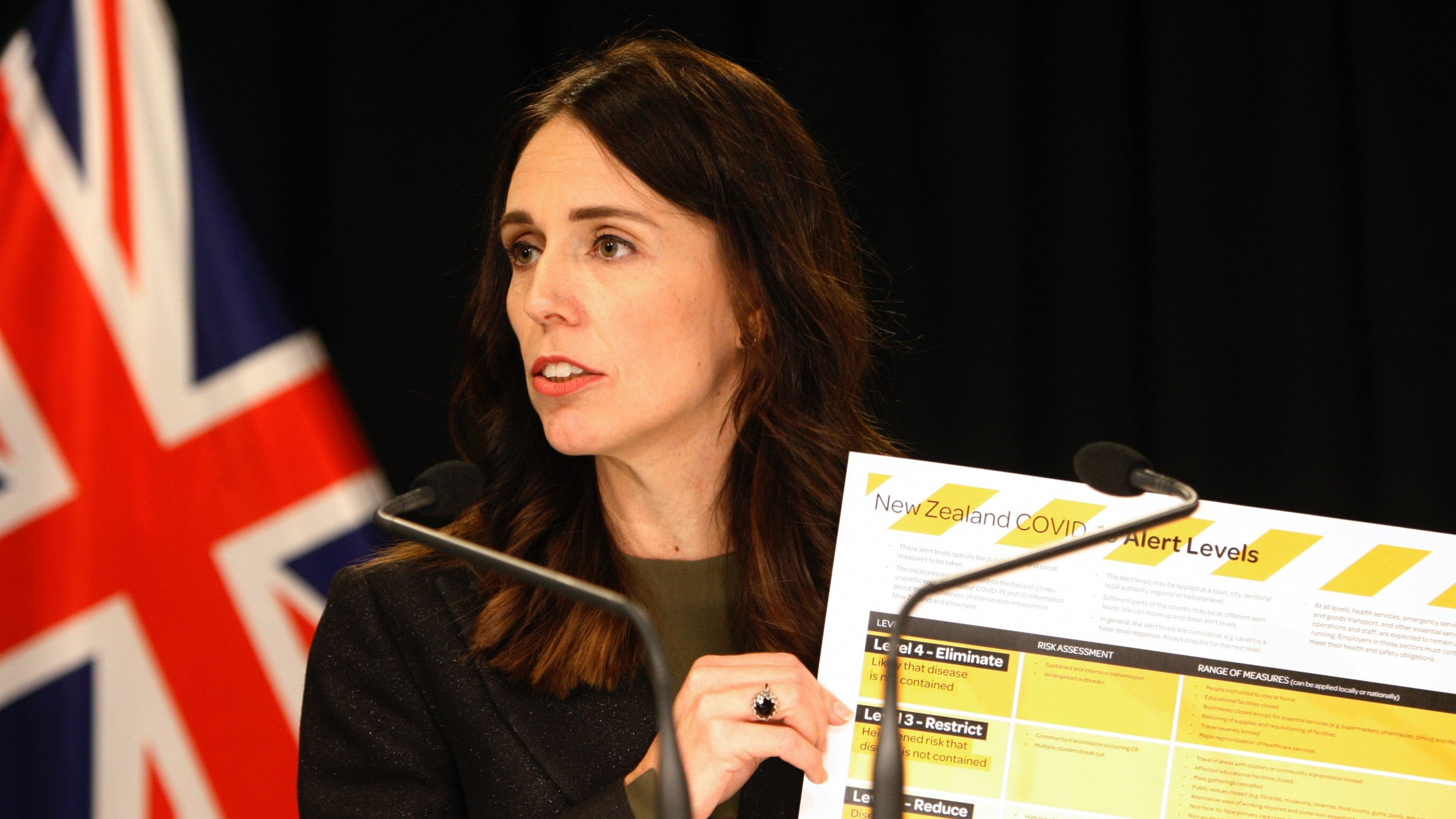 A woman leader holds up a COVID-19 chart card.
