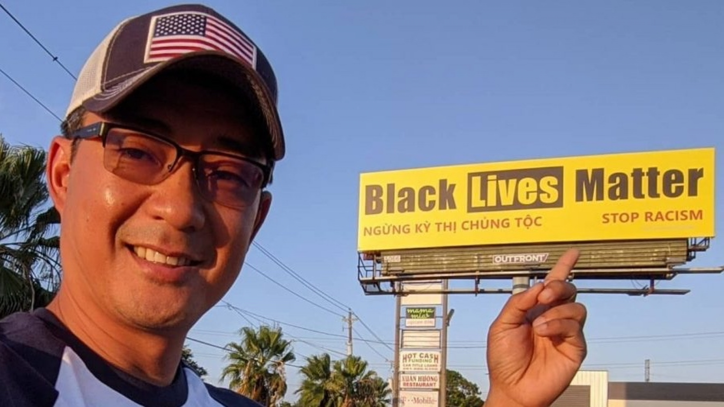 A man points his finger at a yellow billboard with black writing in Vietnamese and English