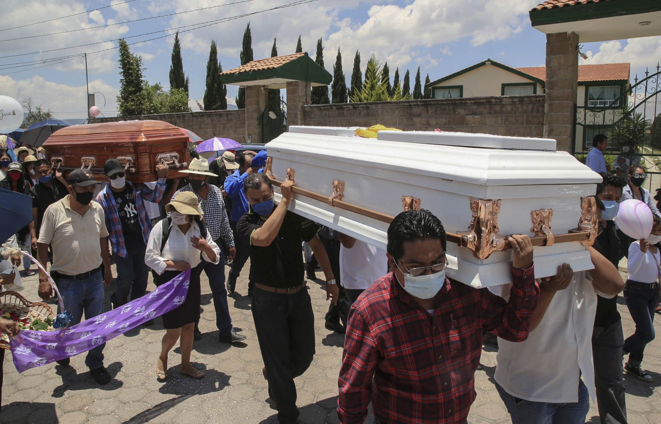 A crowd carries two caskets.