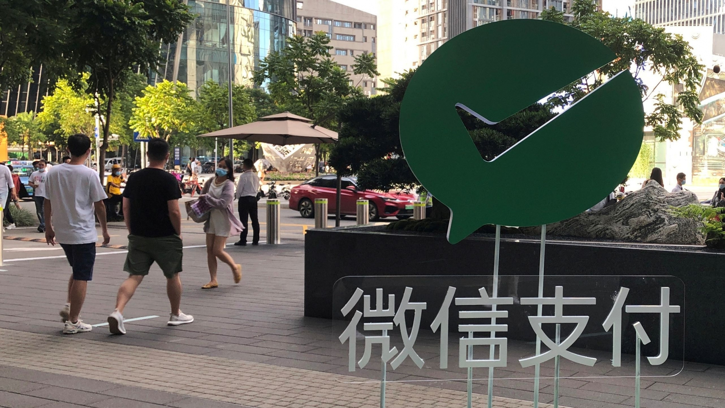People walk past a Wechat Pay sign at the Tencent company headquarters in Shenzhen, Guangdong province, China, Aug. 7, 2020.