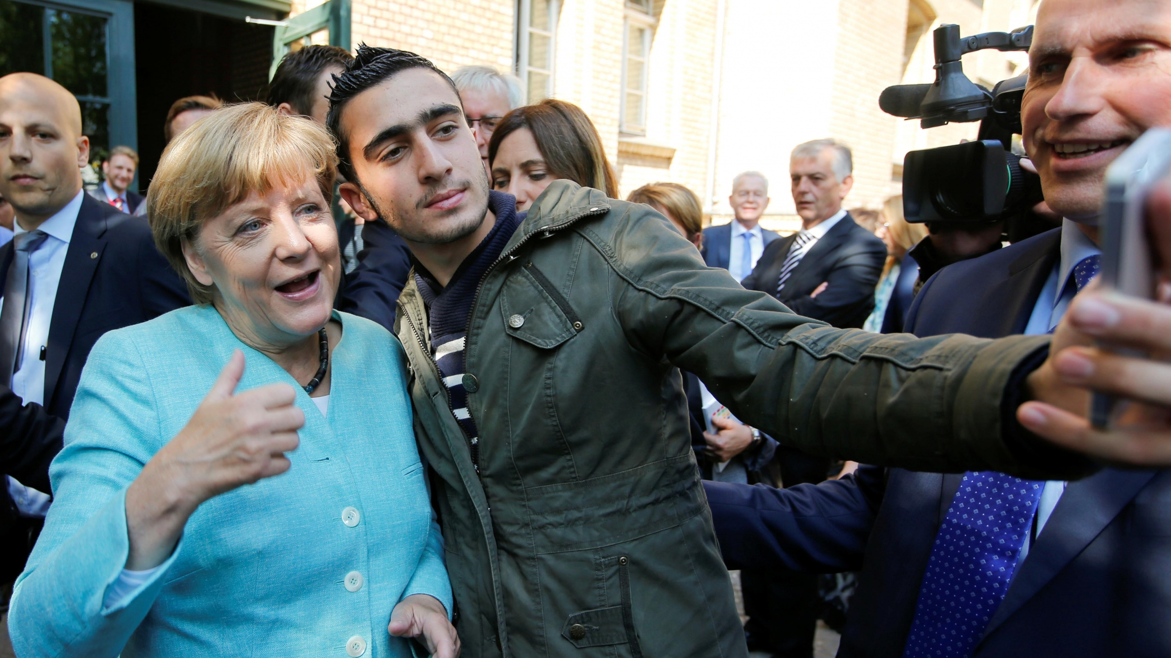 Syrian refugee Anas Modamani takes a selfie with German Chancellor Angela Merkel outside a refugee camp near the Federal Office for Migration and Refugees after registration at Berlin's Spandau district, Germany, on September 10, 2015.