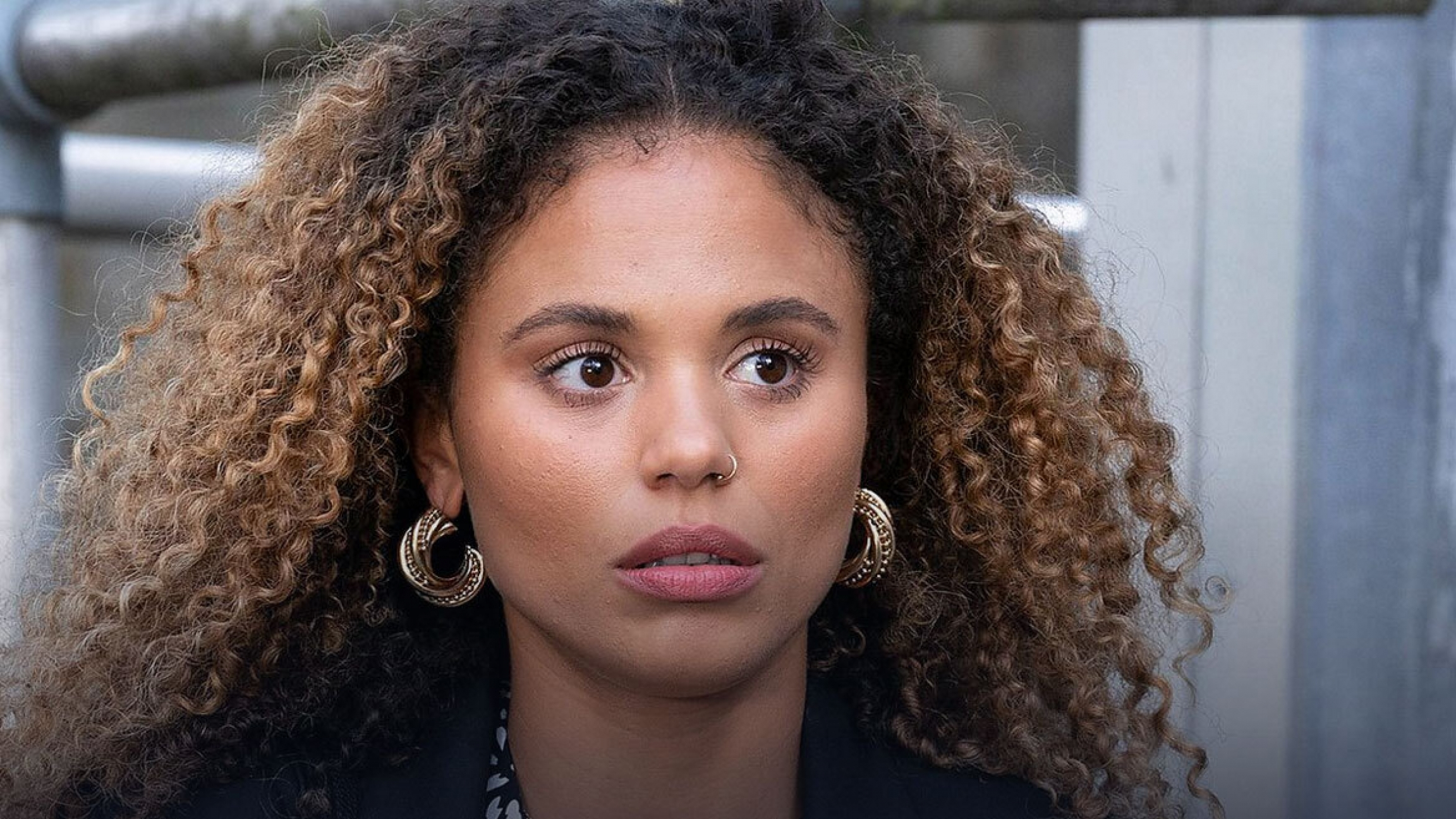 A close-up portrait of a young, light-skinned Black woman with curly hair wearing gold-hooped earrings