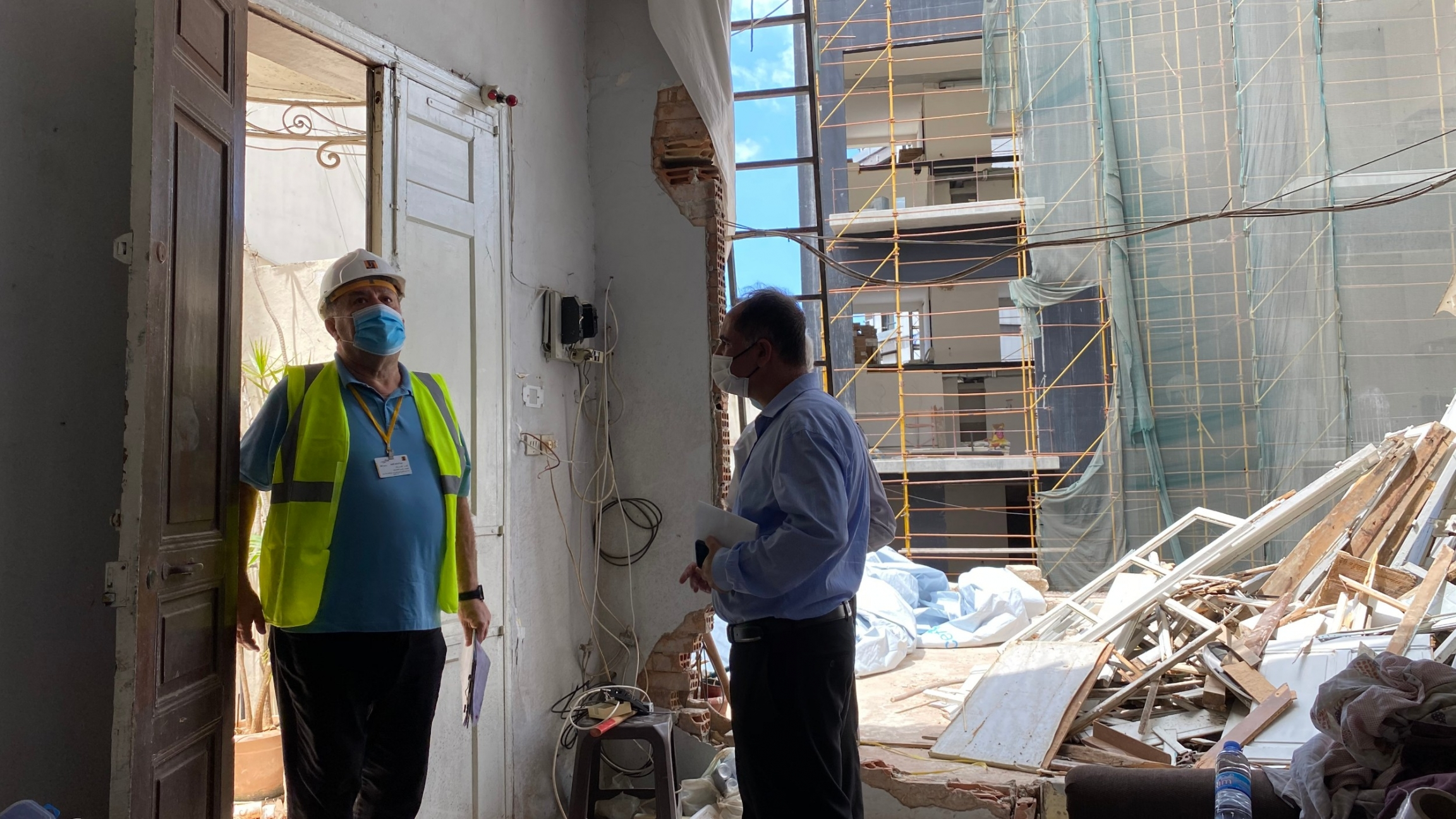 Henri's son Joseph greets an engineer who came tosurvey the damage at the Azar family home in Beirut's Mar Mikhaëldistrict.