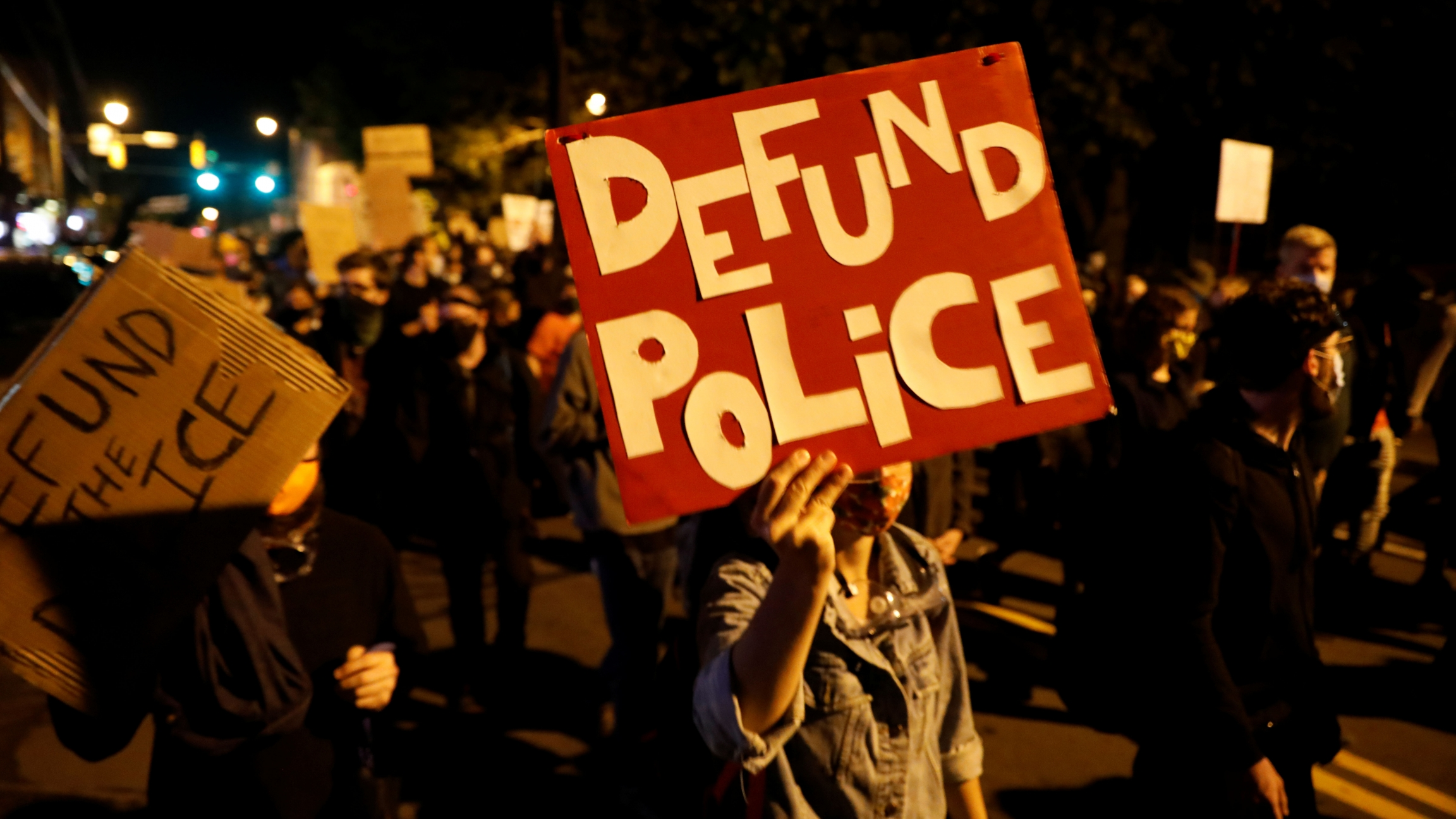 "Demonstrators hold a sign reading ""Defund the police"" during a protest over the death of a Black man, Daniel Prude, after police put a spit hood over his head during an arrest on March 23, in Rochester, New York, September 6, 2020."