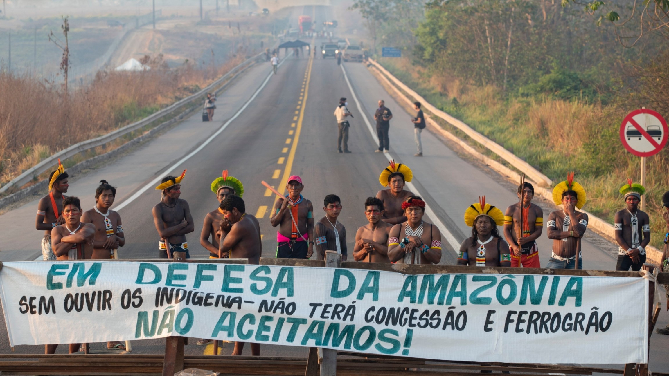"Kayapó Indigenous protesters block highway BR-163 with a banner that reads in Portuguese ""Defending the Amazon. Without listening to Indigenous people, there will be no concession and nor grain railway,"" near Novo Progresso, Pará state, Brazil, Aug. 17, 2"