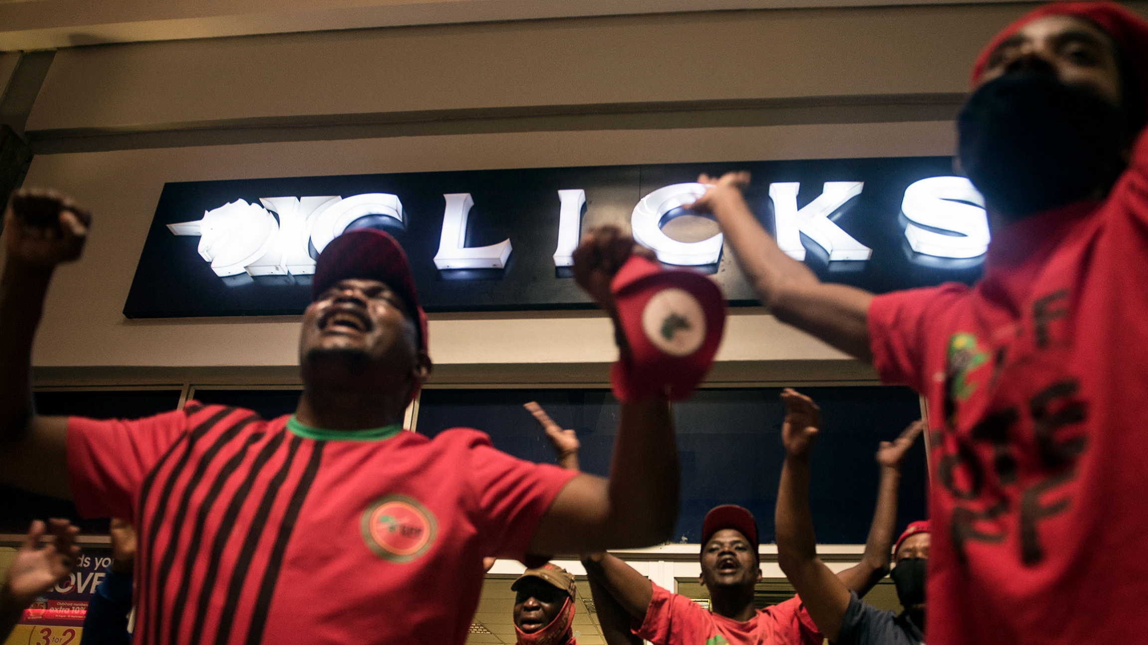 A group of people are shown protesting outside of a Clicks story with their hands raised.