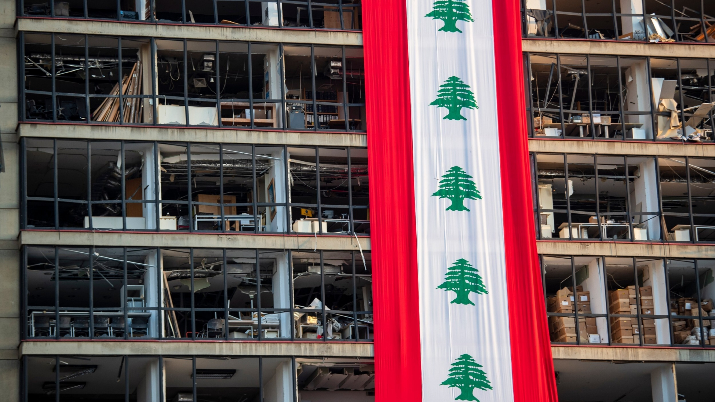 A banner with representations of the Lebanese flag hangs on a damaged building in a neighborhood near the site of the explosion