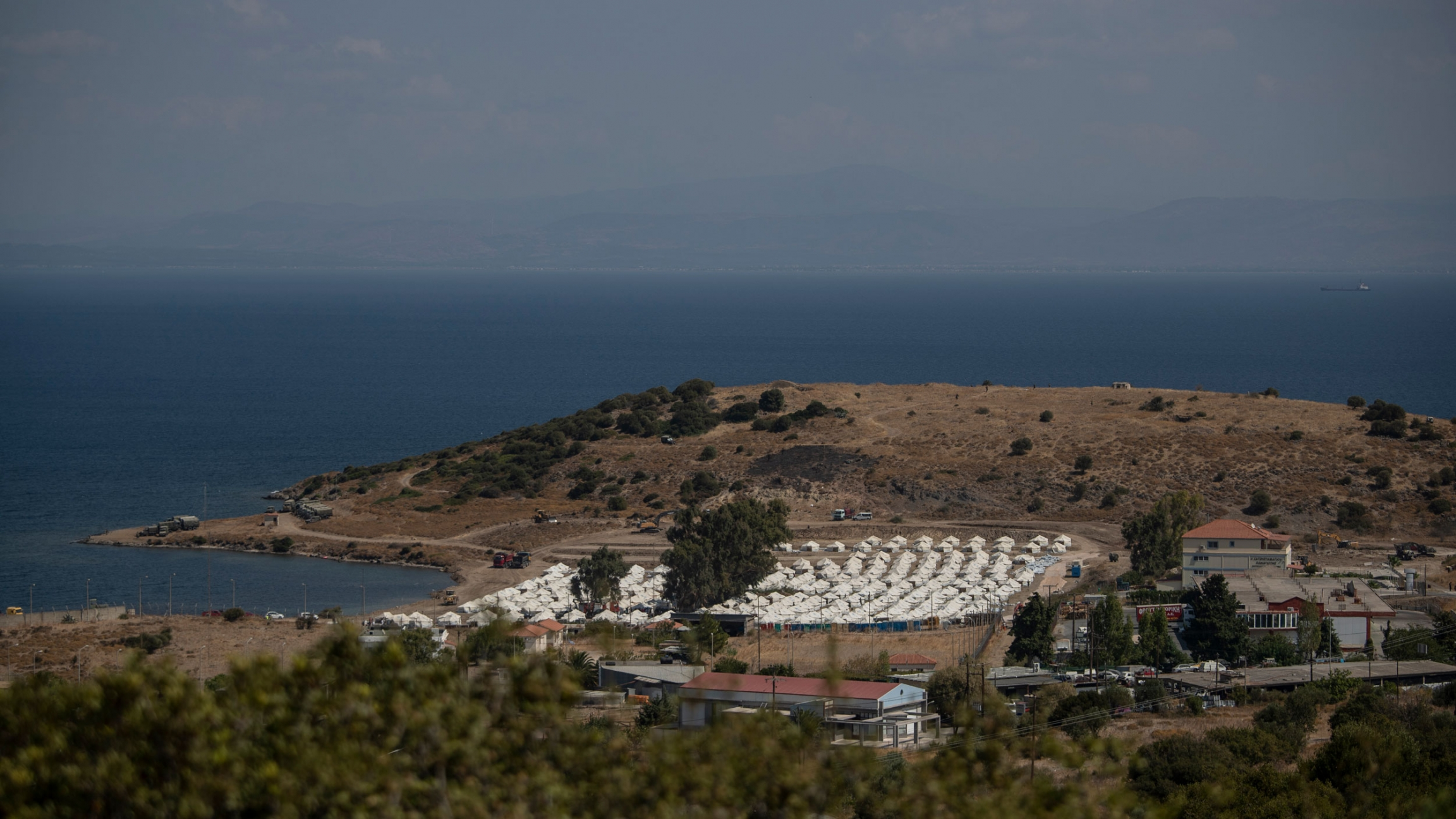A view of a newly constructed camp for asylum-seekers with dozens of rows of white tents and the Aegan Sea in the distance.