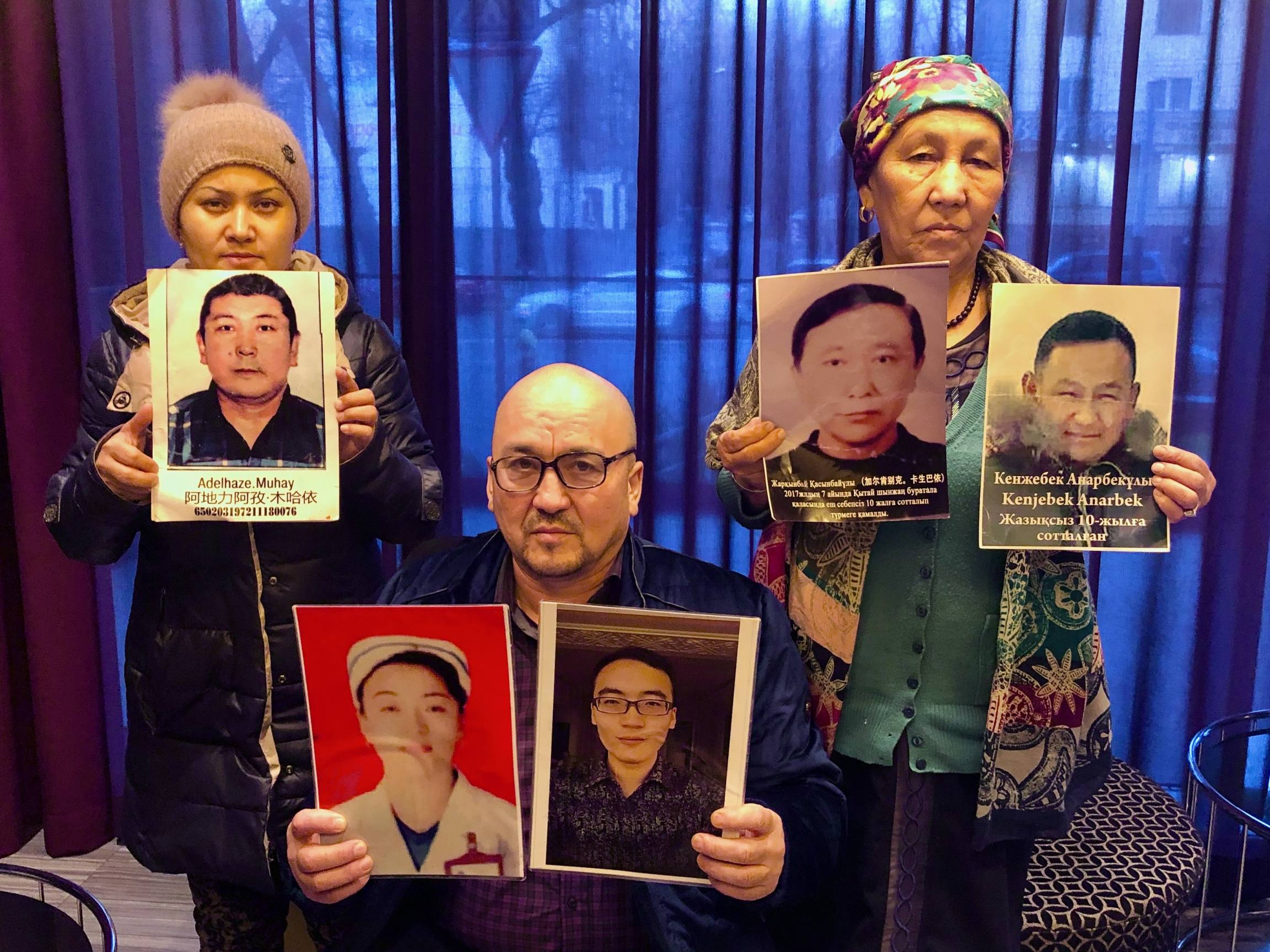 Kazakhs in Almaty hold up photos of their relatives being held in detention in Xinjiang, China.