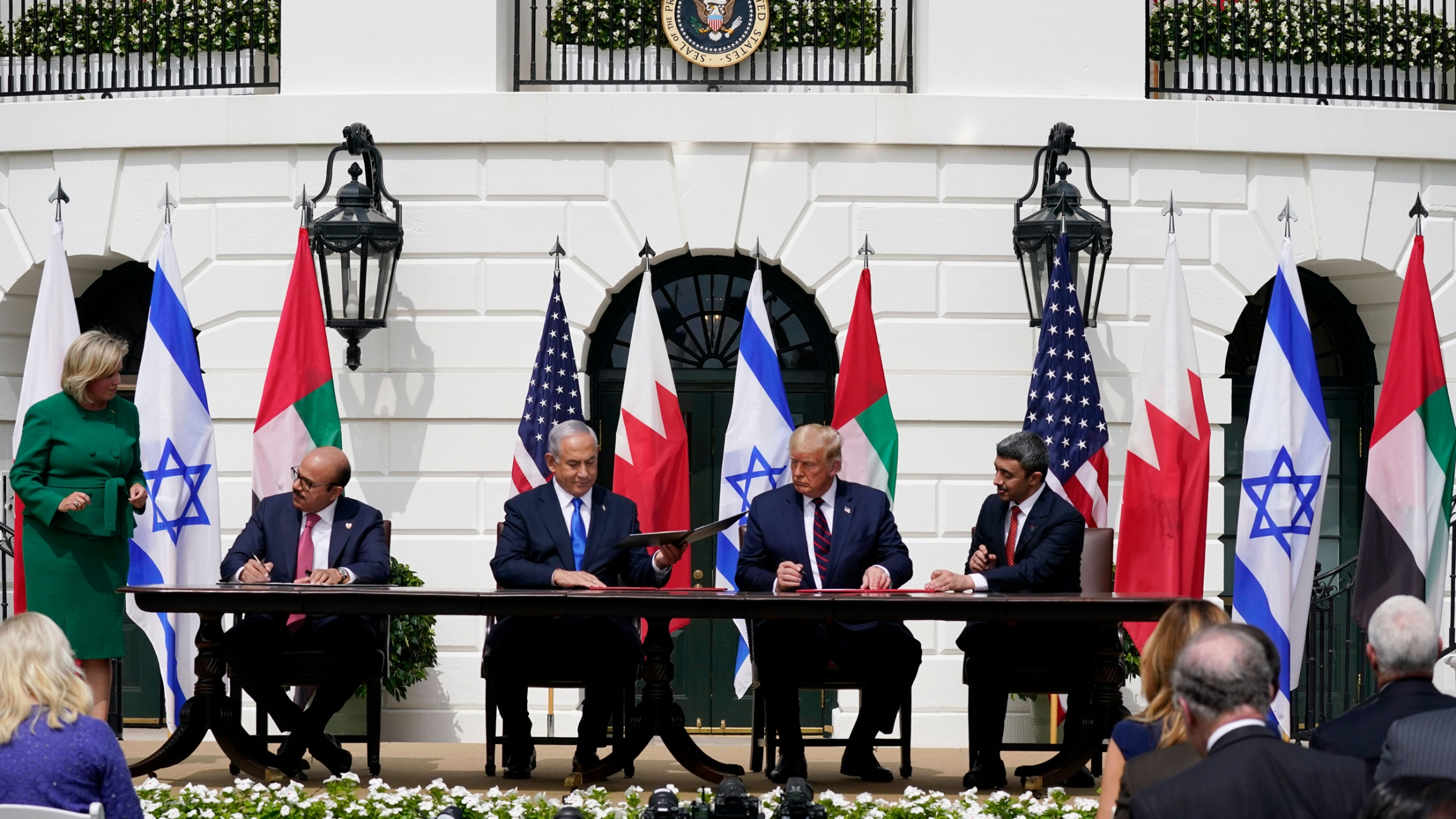 The leaders of the US, UAE, Israel and Bahrain are shown wearing suits and sitting at a table signing documents with flags from each country behind them.