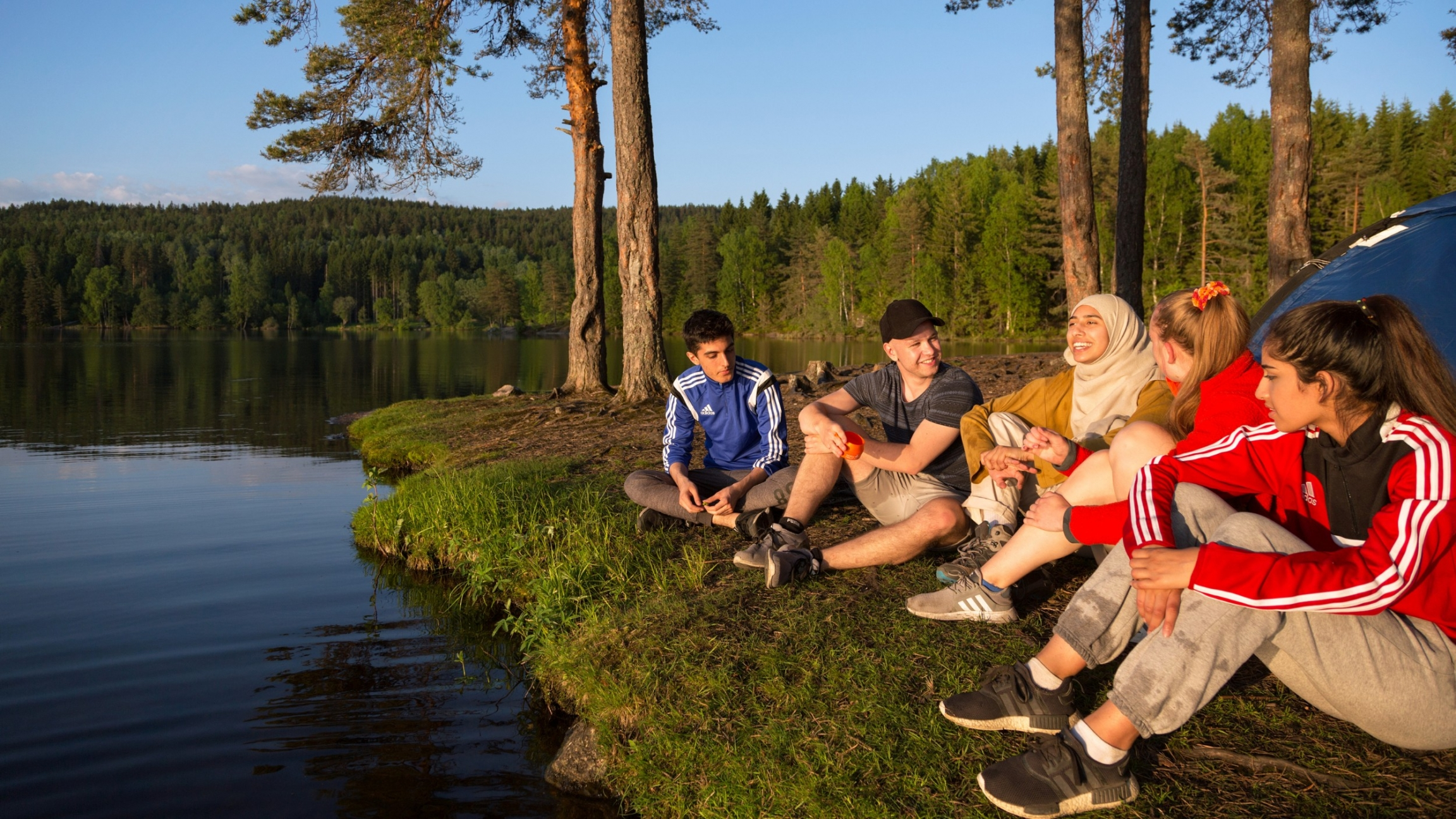 Norwegian youth sit on the ground while spending time outdoors on a lake.