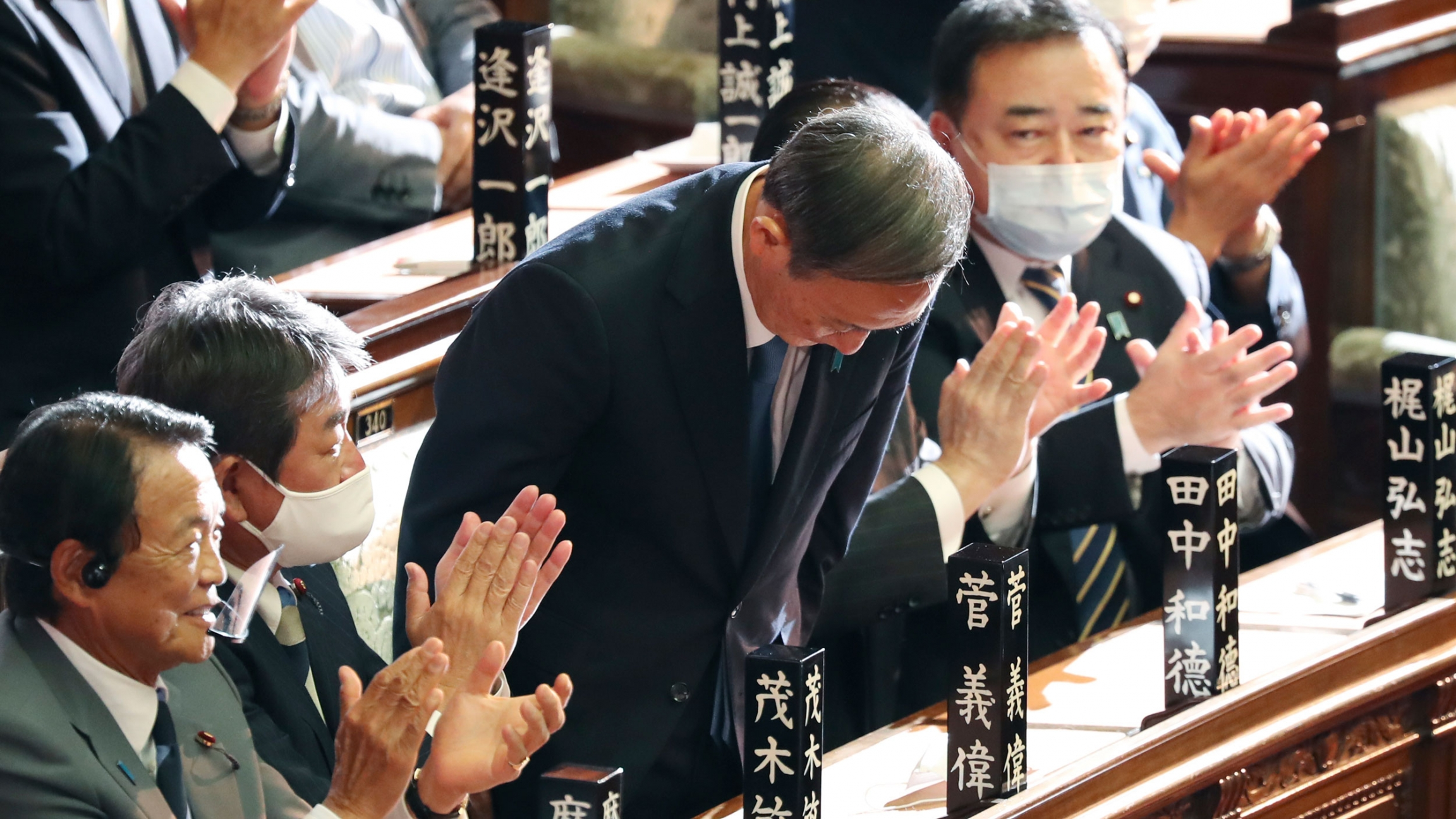 Yoshihide Suga is shown bowing and surrounded by parliamentarians on either side clapping their hands.