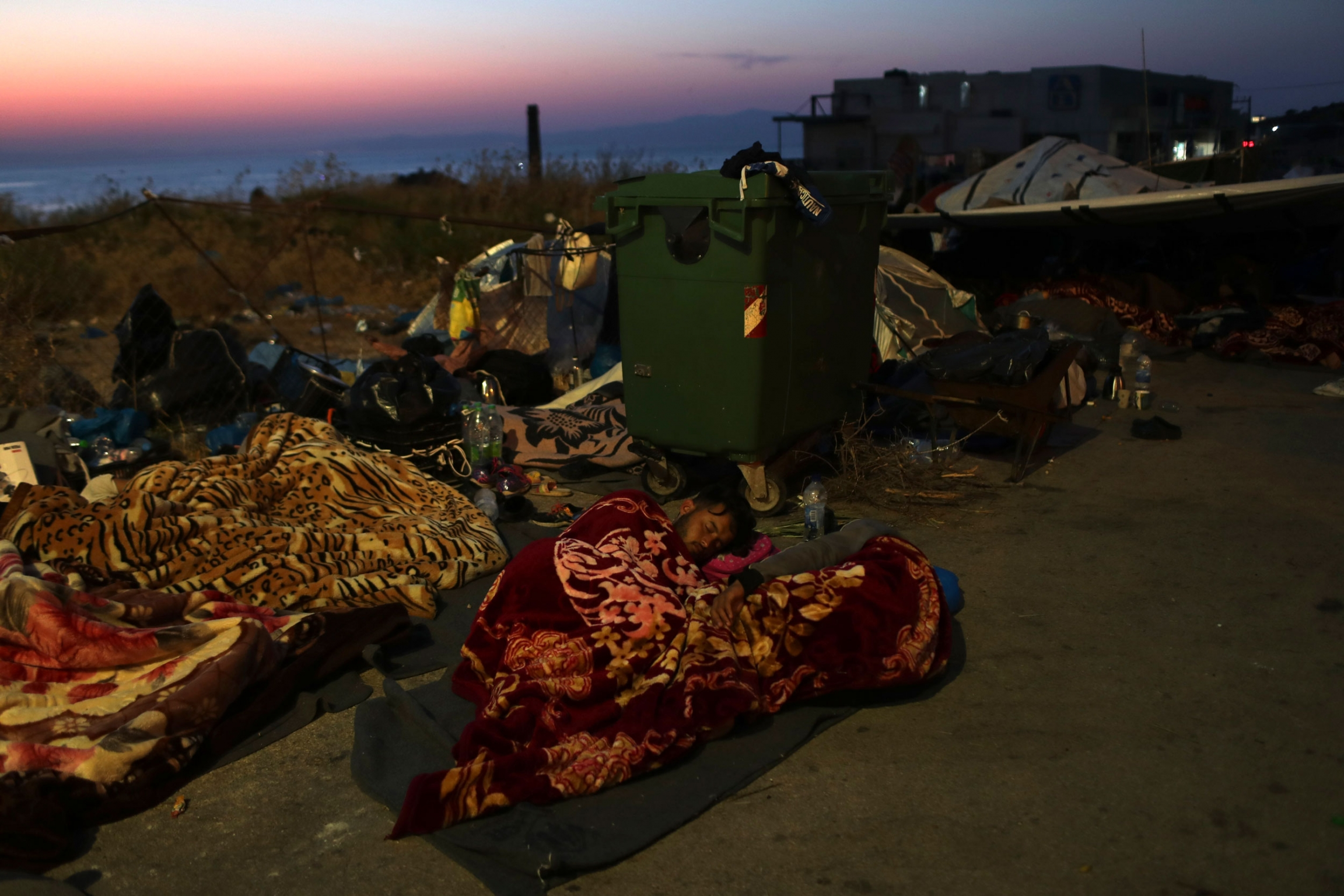 Several migrants and refugees are shown sleeping under blankets on the side of a road with a green trash bin with wheels nearby.
