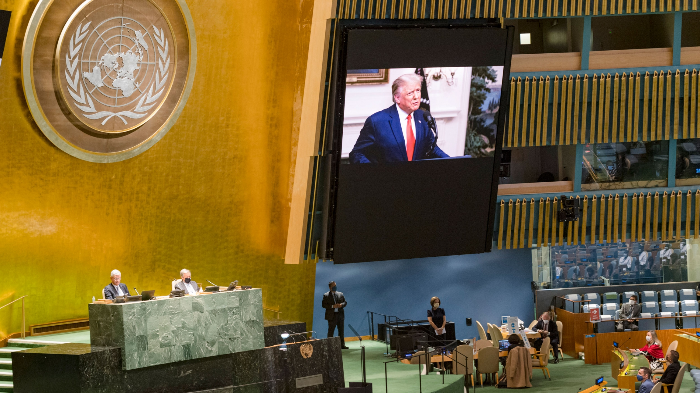 US President Donald Trump, shown on a large video screen against a gold leaf wall and the United Nations symbol.