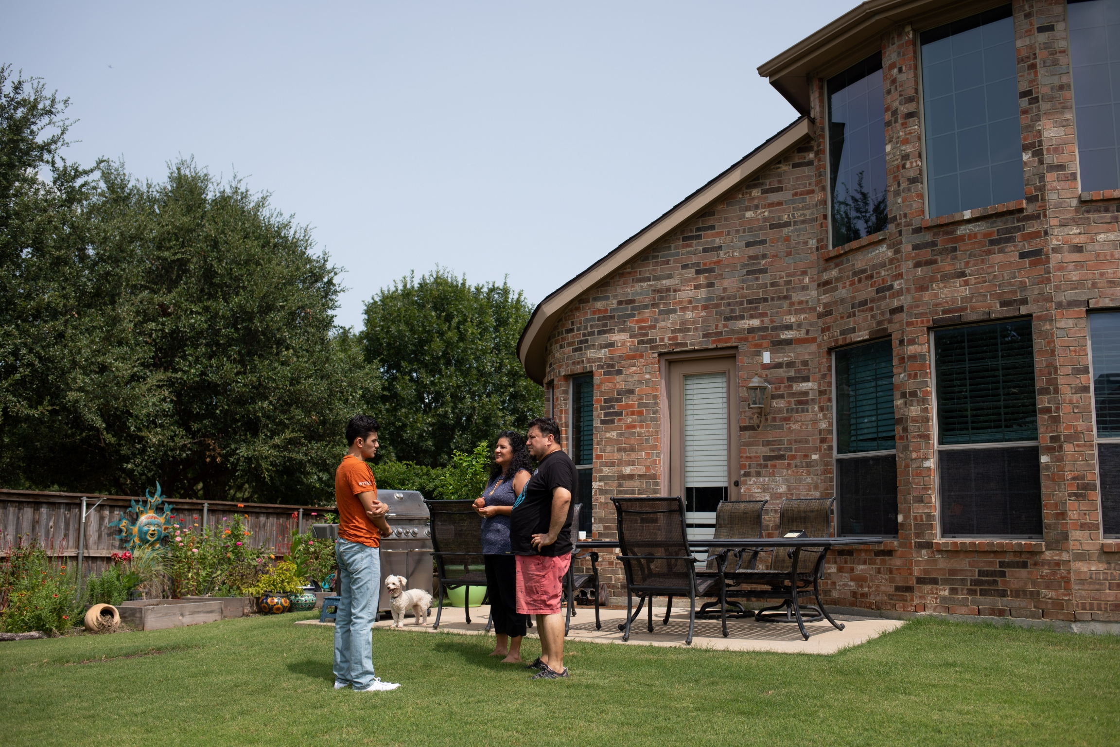Izcan Ordaz, left, and his parents in the backyard of their home in Fort Worth, Texas.