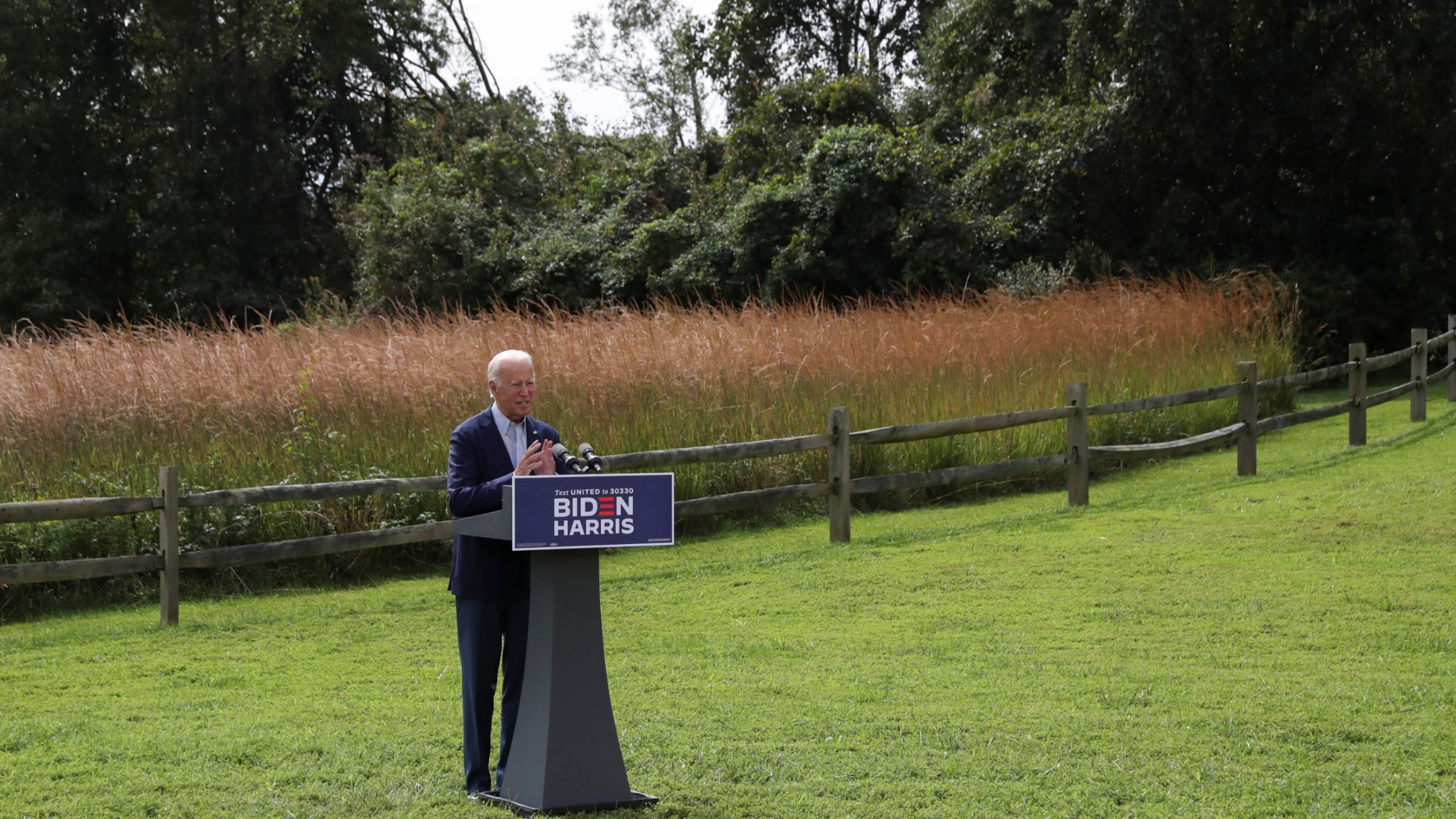 Standing in a grassy field, Joe Biden speaks about climate change during a campaign event held outside the Delaware Museum of Natural History in Wilmington, Delaware, Sept. 14, 2020.