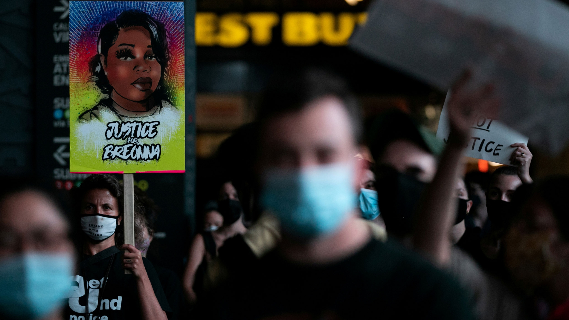 A large crowd of people are shown in the dark of night with a woman holding a placard with an illustration of Breonna Taylor on it.
