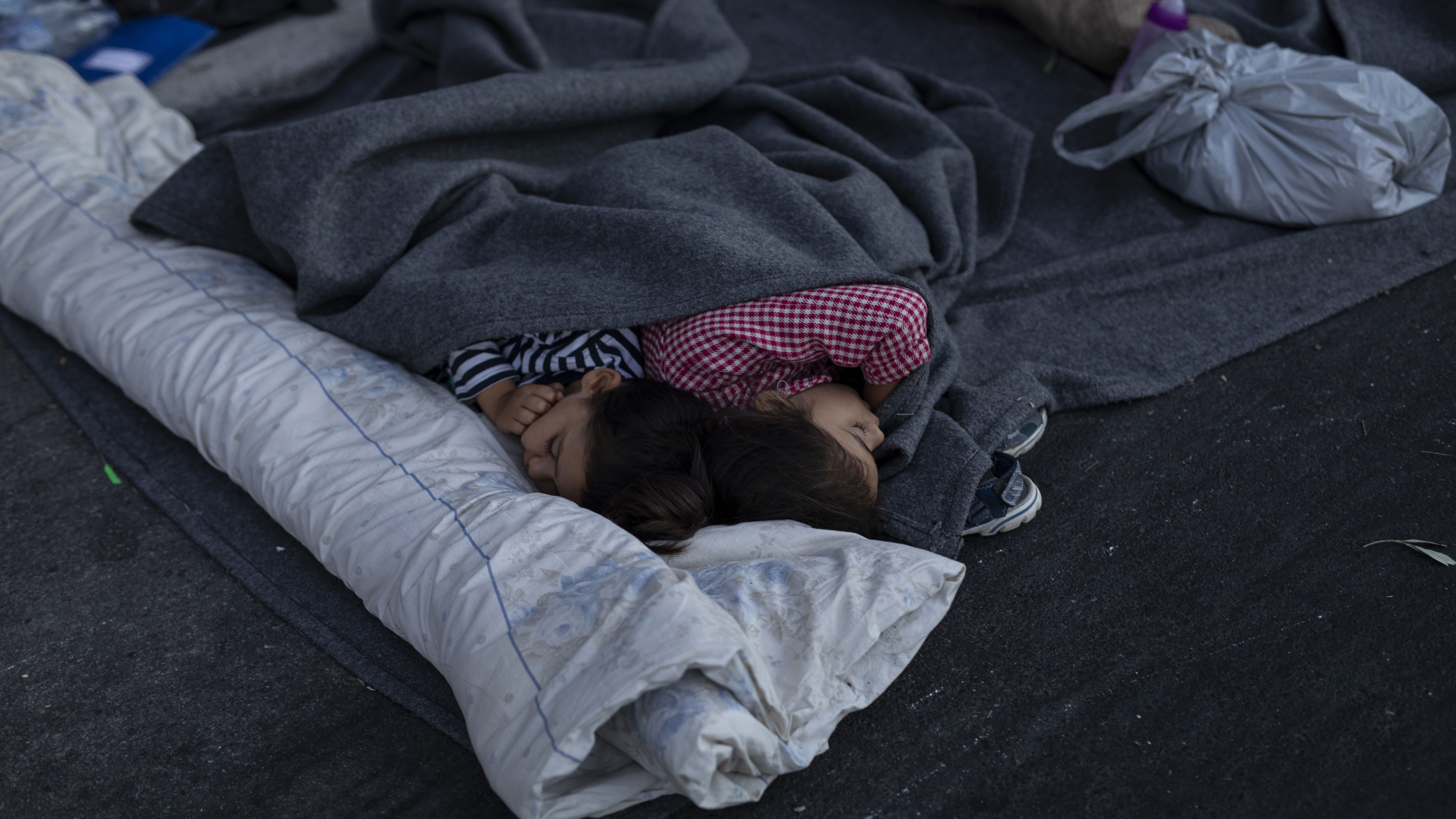 Two children sleep beneath gray blankets on the road near the Moria refugee camp on the northeastern island of Lesbos, Greece, Sept. 10, 2020.