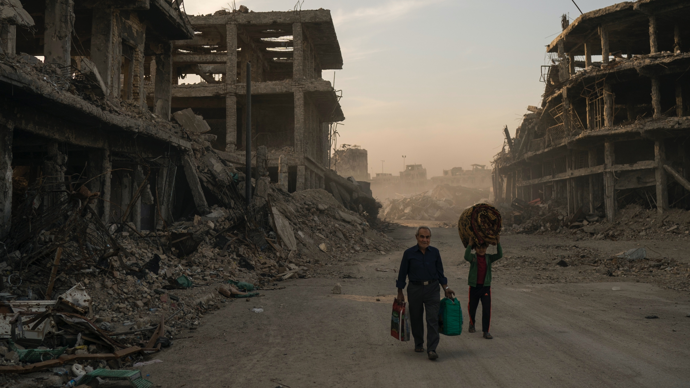 Two people carry luggage down a bombed out street in Mosul.