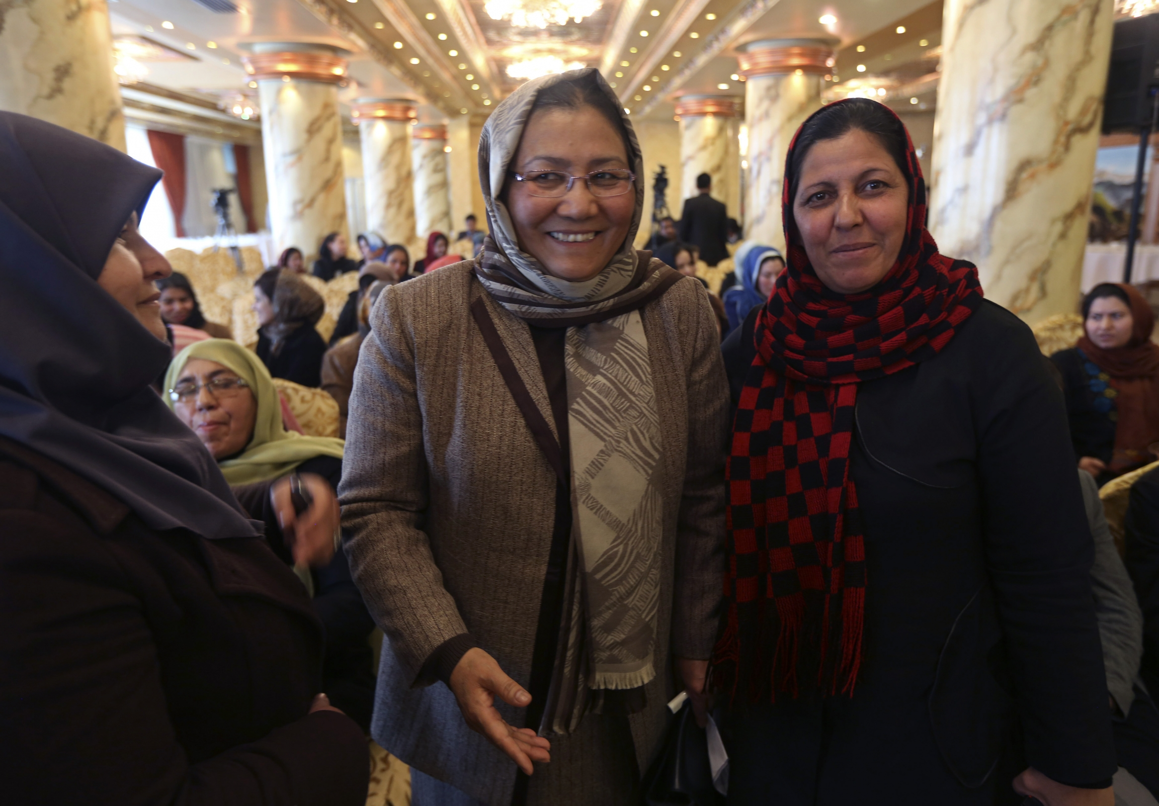 Three women wearing headscarves stand together and the one in the middle, wearing glasses, smiles.
