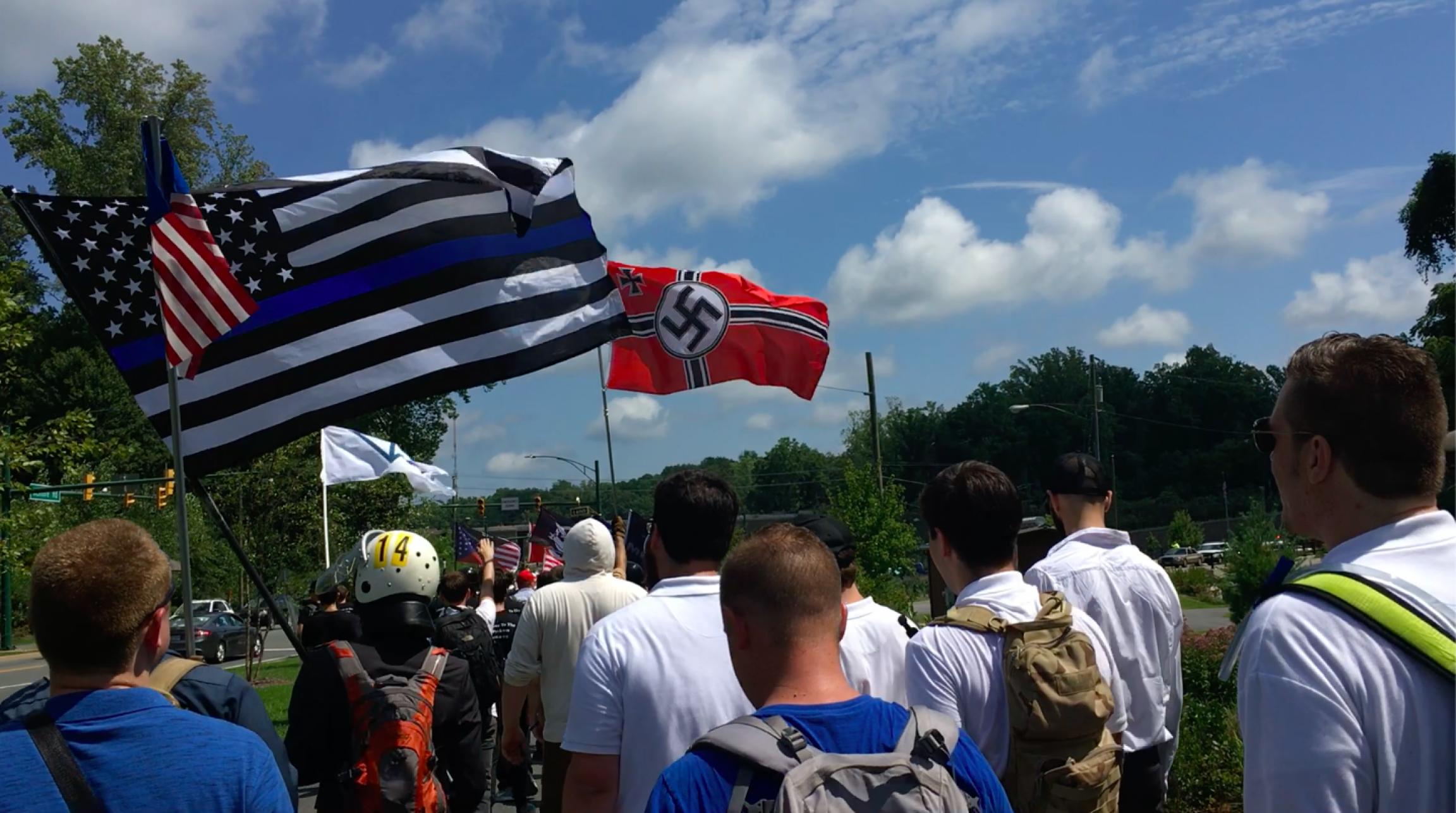 White men walk down a street with white power flags showing Nazi symbols