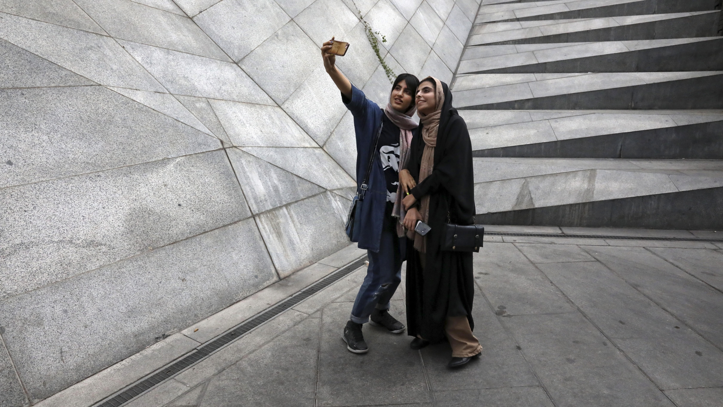 Two Iranian women take a selfie outside a shopping mall in northern Tehran, Iran, on July 2, 2019.
