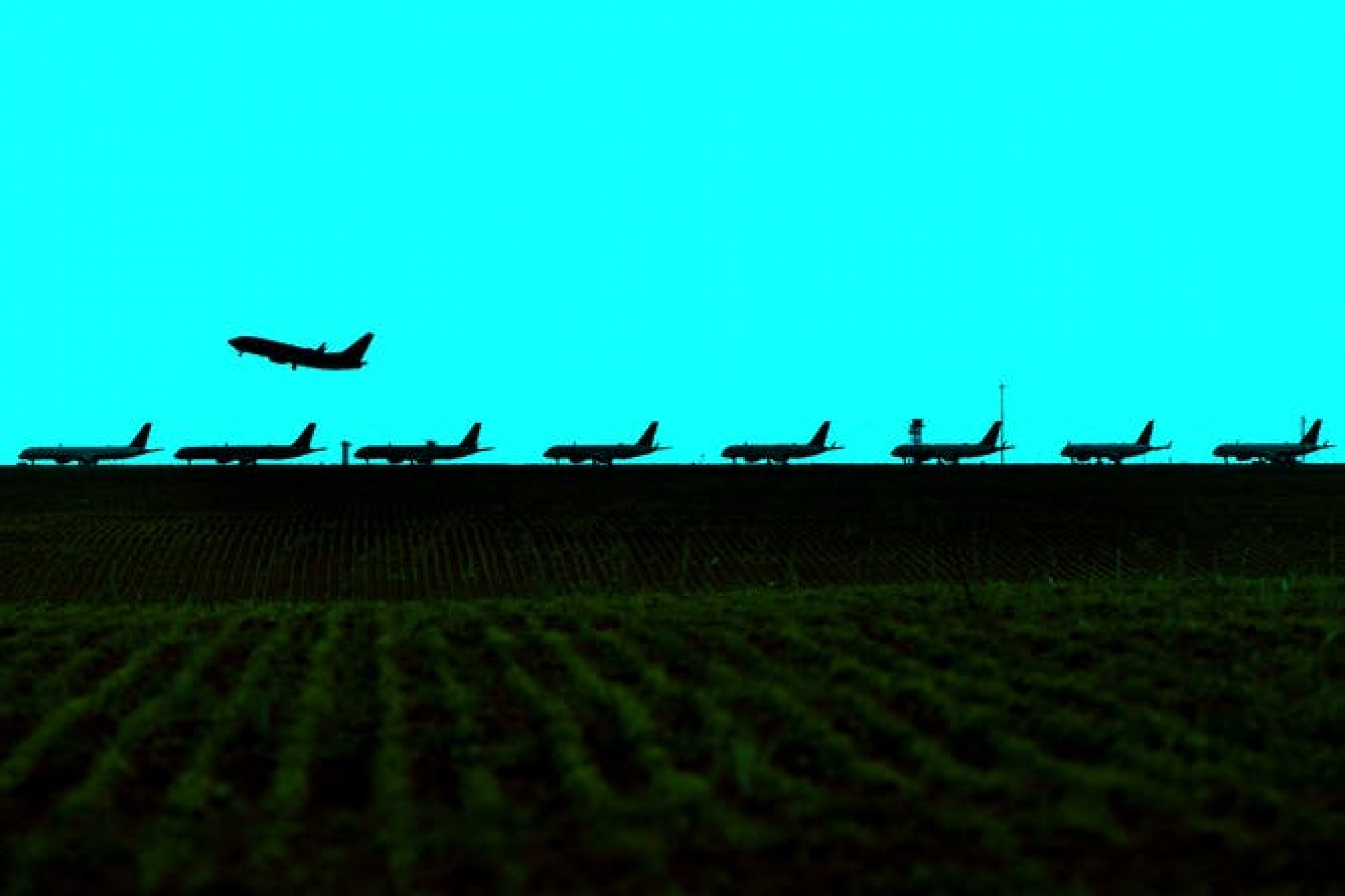 A silhouette of passenger jets lined up on a runway.